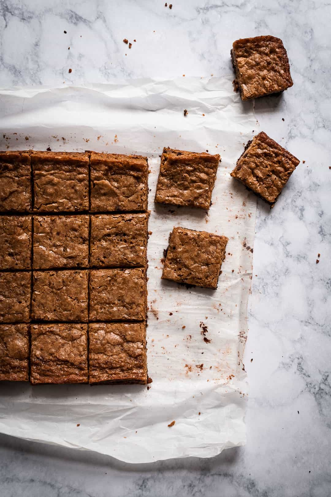 butterscotch dark chocolate bars on parchment paper cooling on a marble countertop