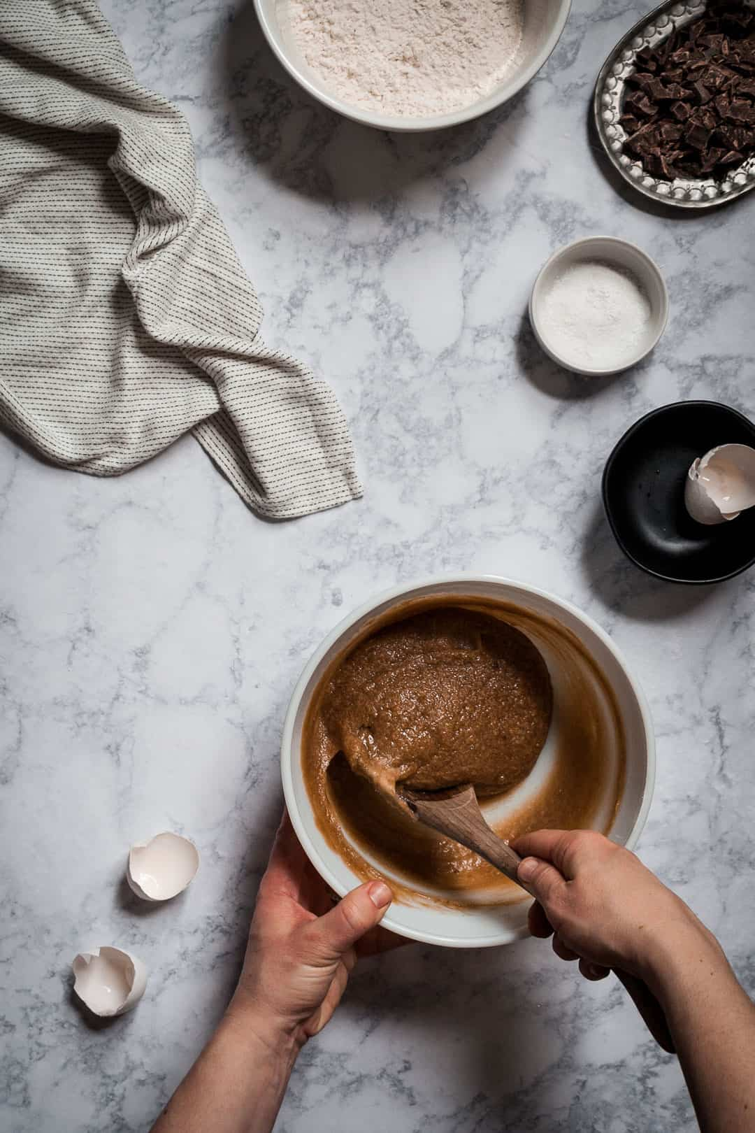 hands holding a spoon and stirring a bowl of butterscotch dark chocolate blondie bar cookie batter; kitchen process