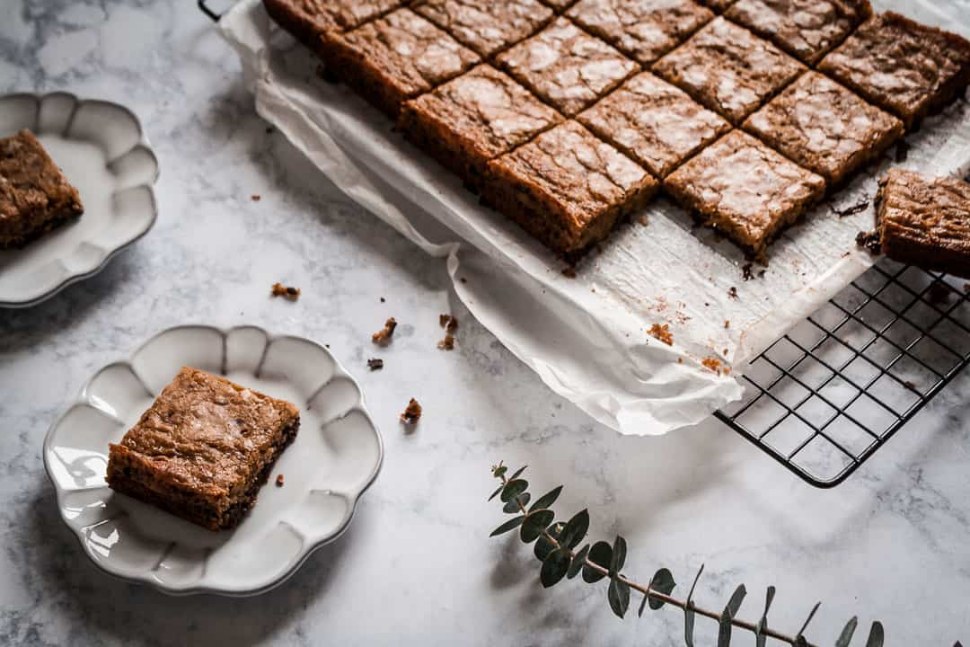 butterscotch dark chocolate bars cooling on a marble countertop and backlit with natural light