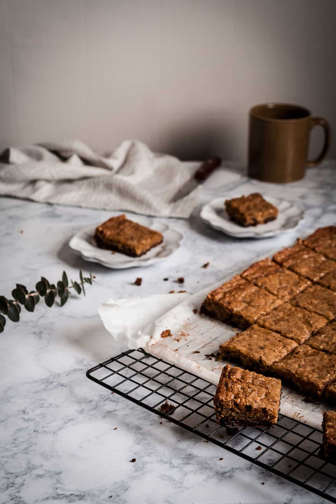 kitchen scene of butterscotch dark chocolate bars cooling on a marble counter with a knife and mug of coffee nearby