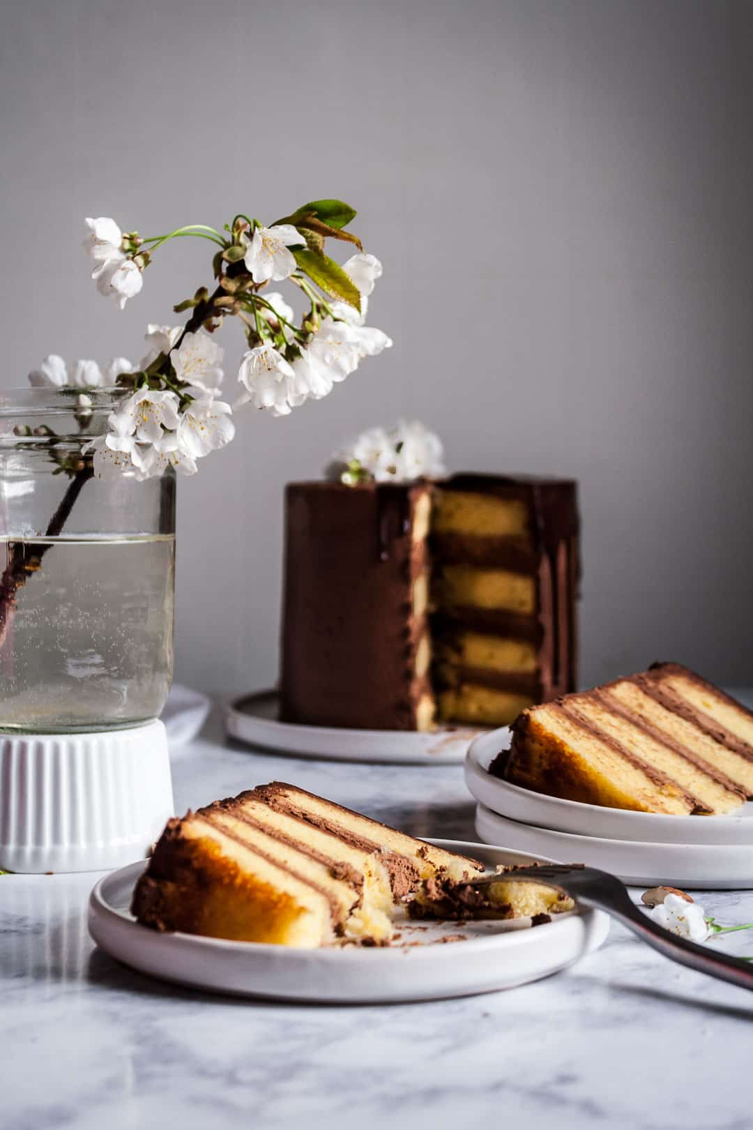 marzipan cake with chocolate buttercream and chocolate ganache drip on a white platter and marble surface, with two pieces cut and plated on white plates next to a vase of white cherry blossoms
