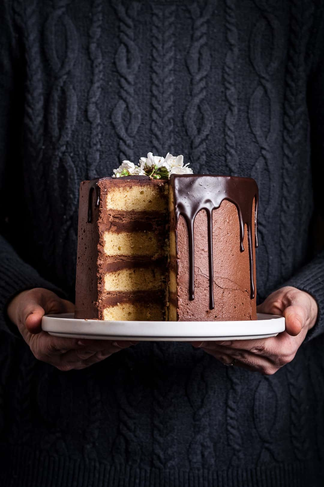closeup of yellow marzipan cake with dark chocolate buttercream with a slice missing, on a white platter being held by a person wearing a navy blue cable knit sweater