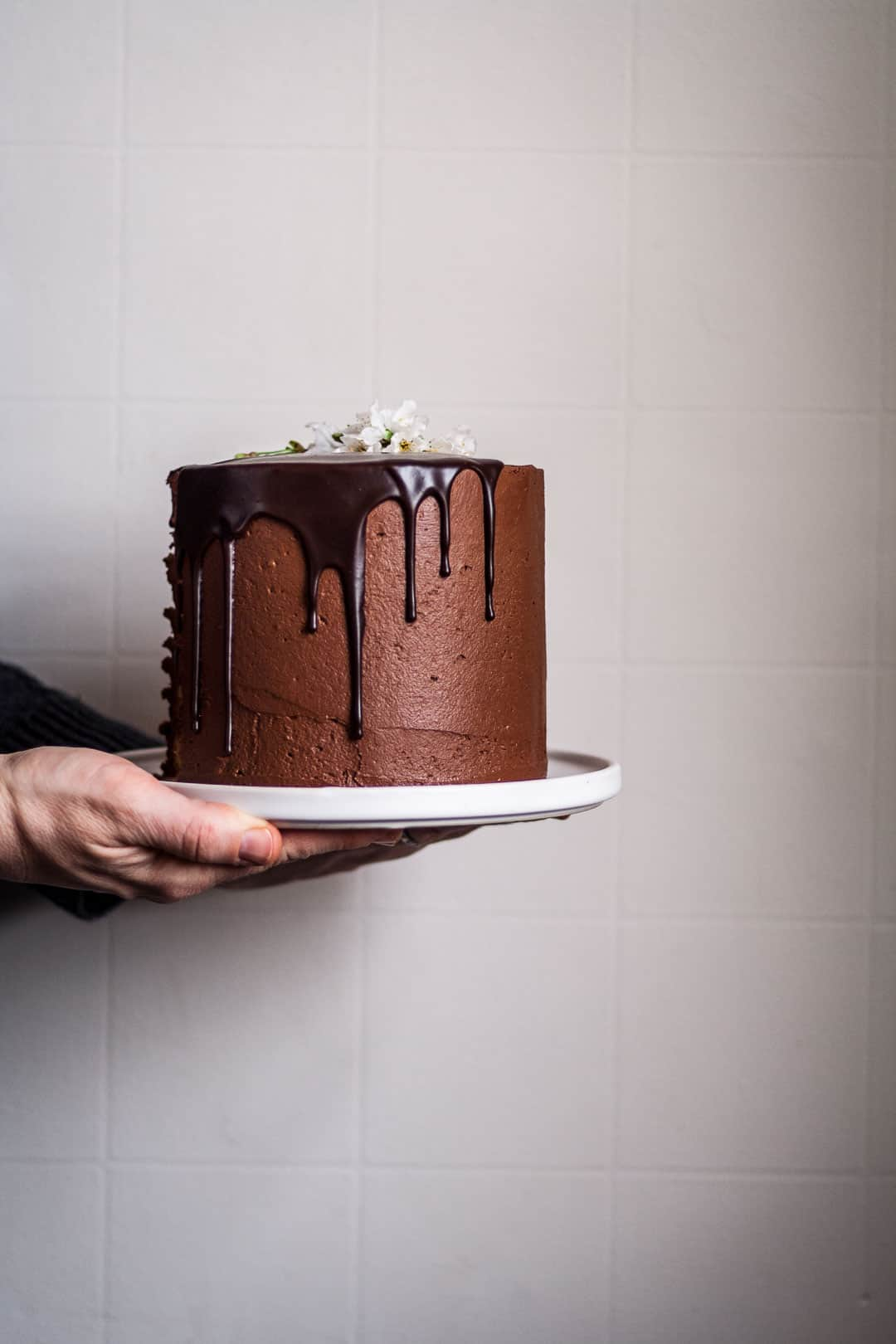 two hands holding marzipan cake with chocolate buttercream and chocolate ganache drip on a white platter against a white wall