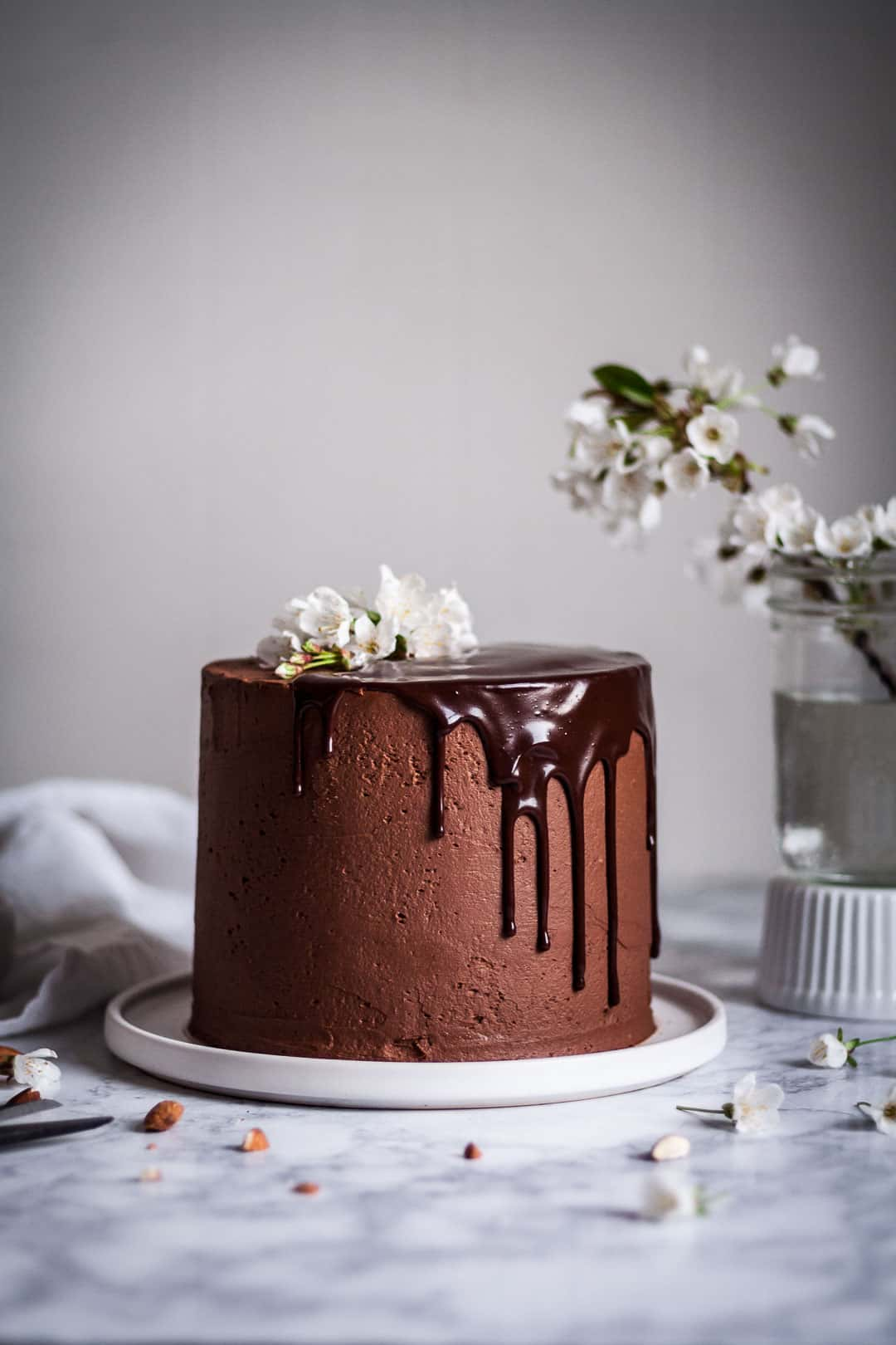 marzipan cake with chocolate buttercream and chocolate ganache drip on a white platter and marble surface, next to a vase of white cherry blossoms