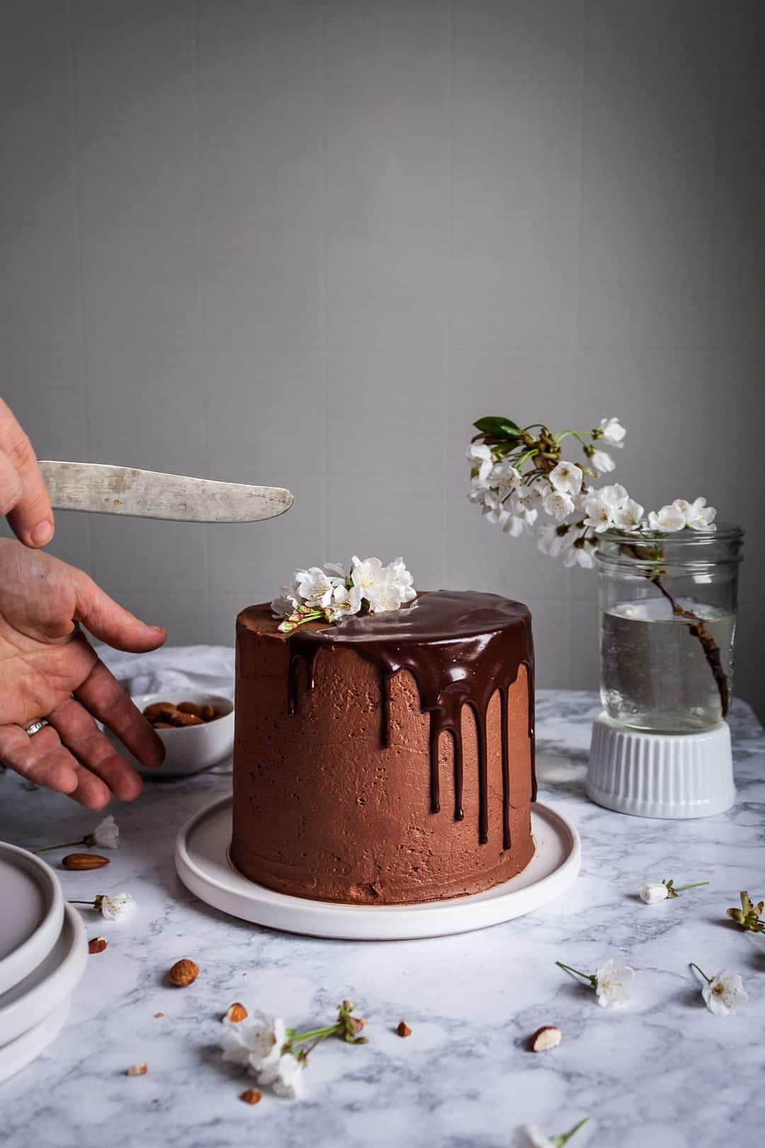 hands holding a knife and reaching out towards marzipan cake with dark chocolate buttercream sitting on a marble surface