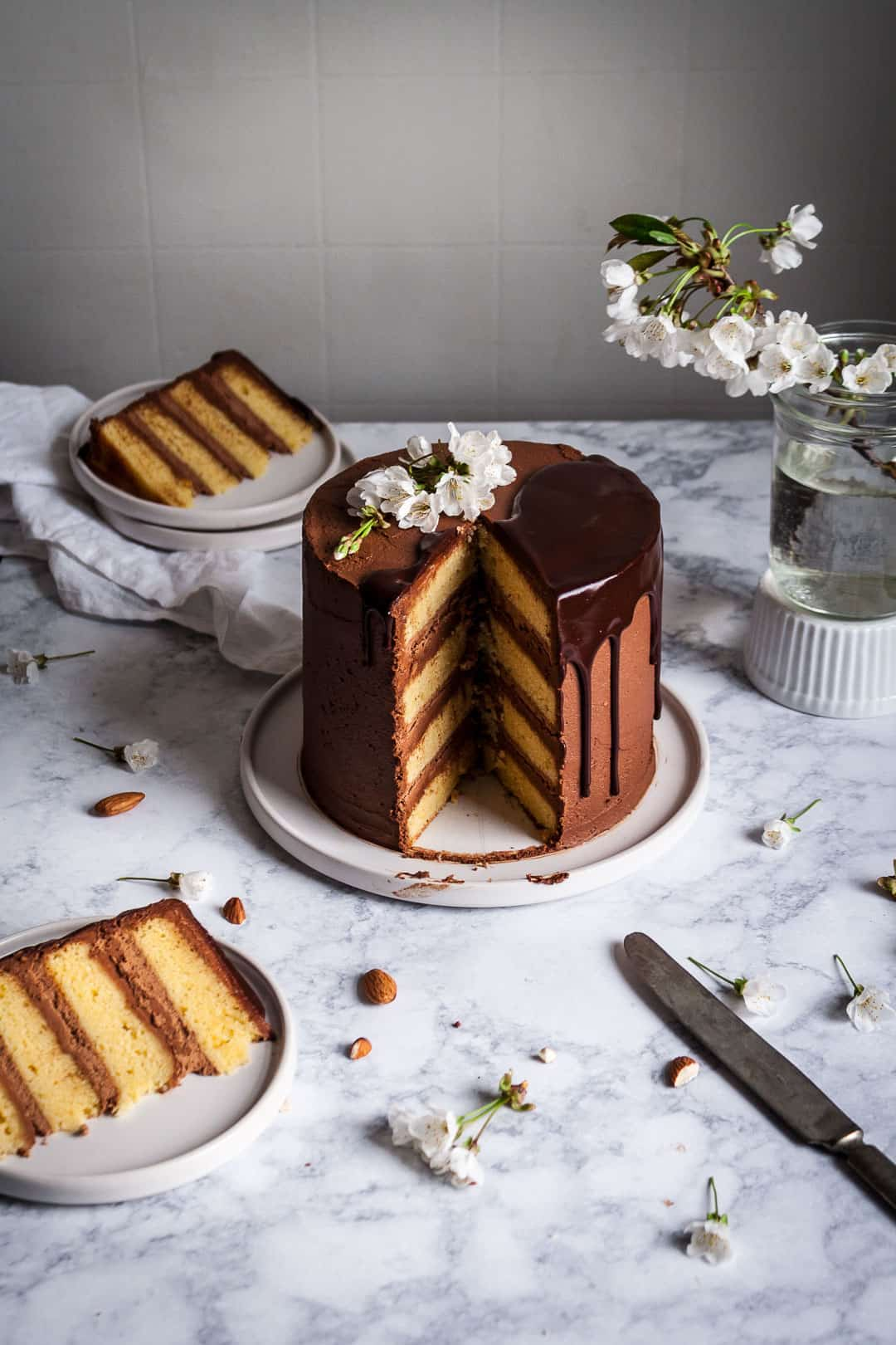 side view of marzipan cake with dark chocolate buttercream with two slices cut out and plated next to the cake on a marble surface