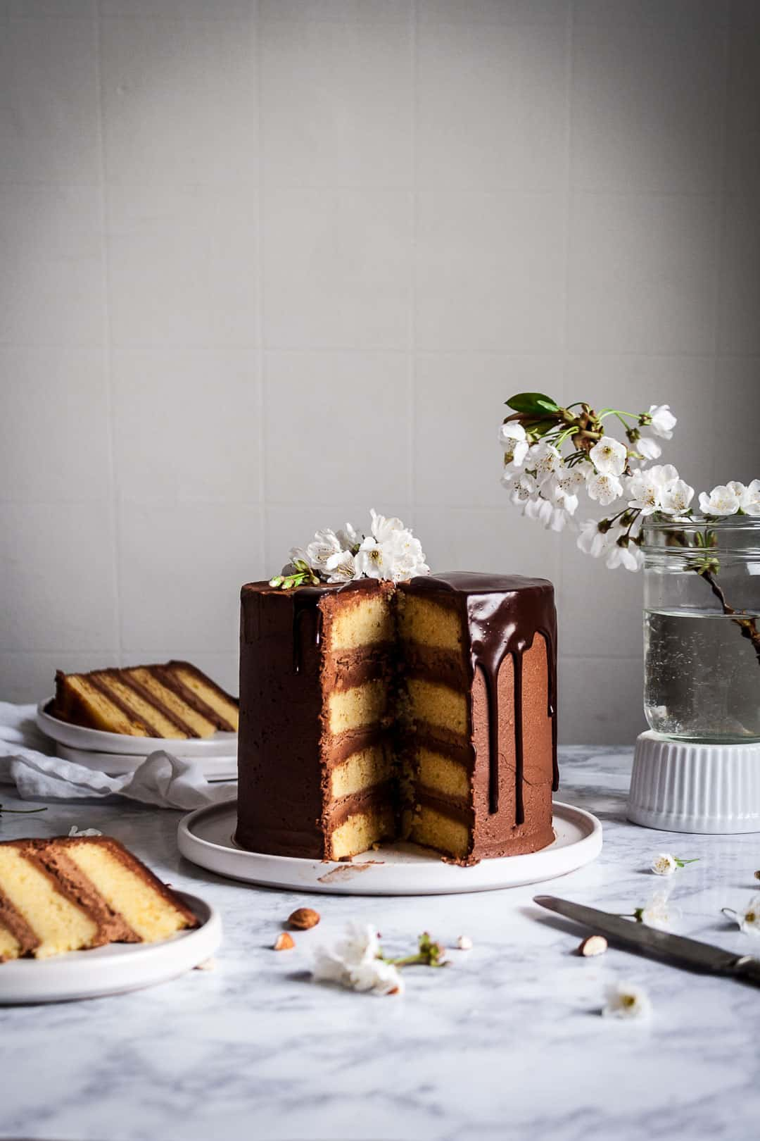 Marzipan and dark chocolate layer cake on white platter and marble background with cherry blossom garnish on the cake