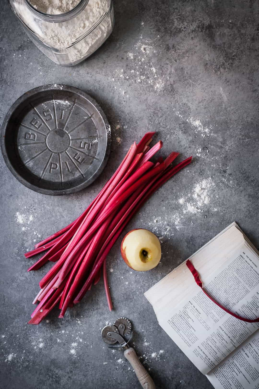 making a rhubarb apple pie with ginger and lemongrass: top view of rhubarb stalks and peeled apple on grey surface with opened cookbook, metal pie tin and flour container nearby