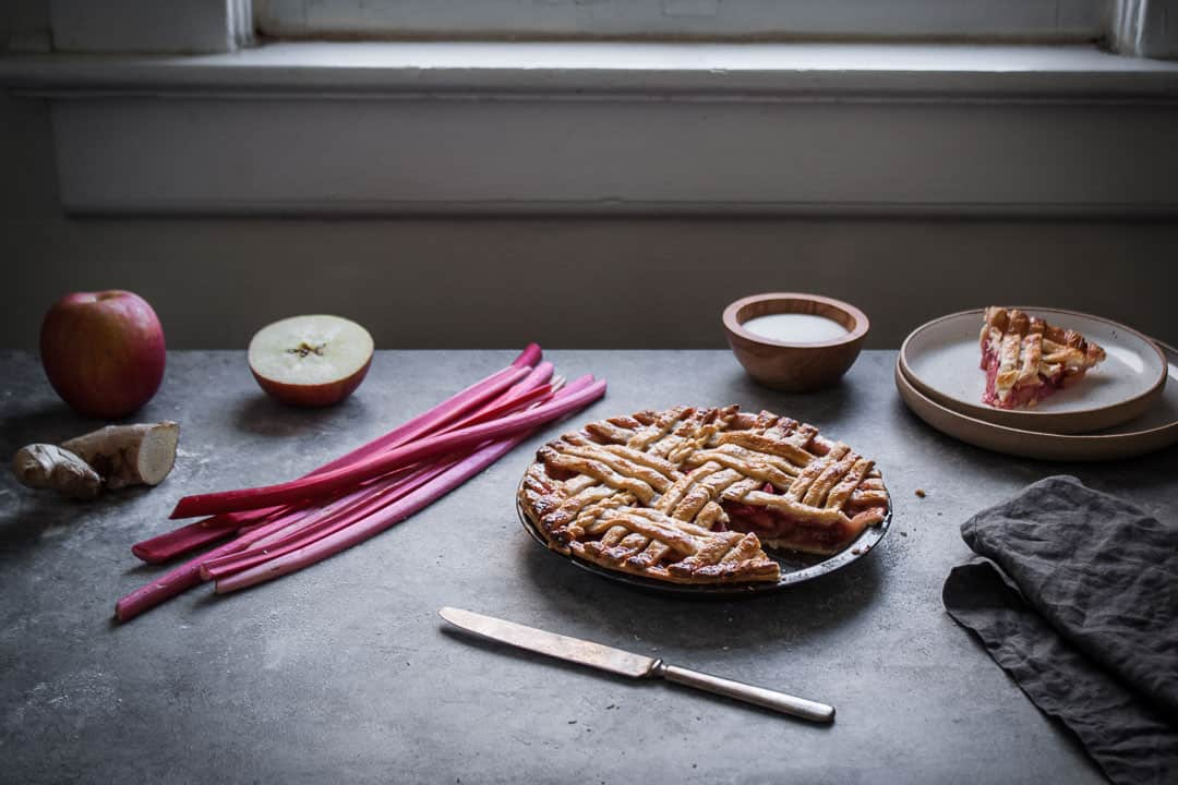 backlit image of baked rhubarb apple pie with ginger and lemongrass next to a window with a slice cut out on a plate nearby along with the pie ingredients