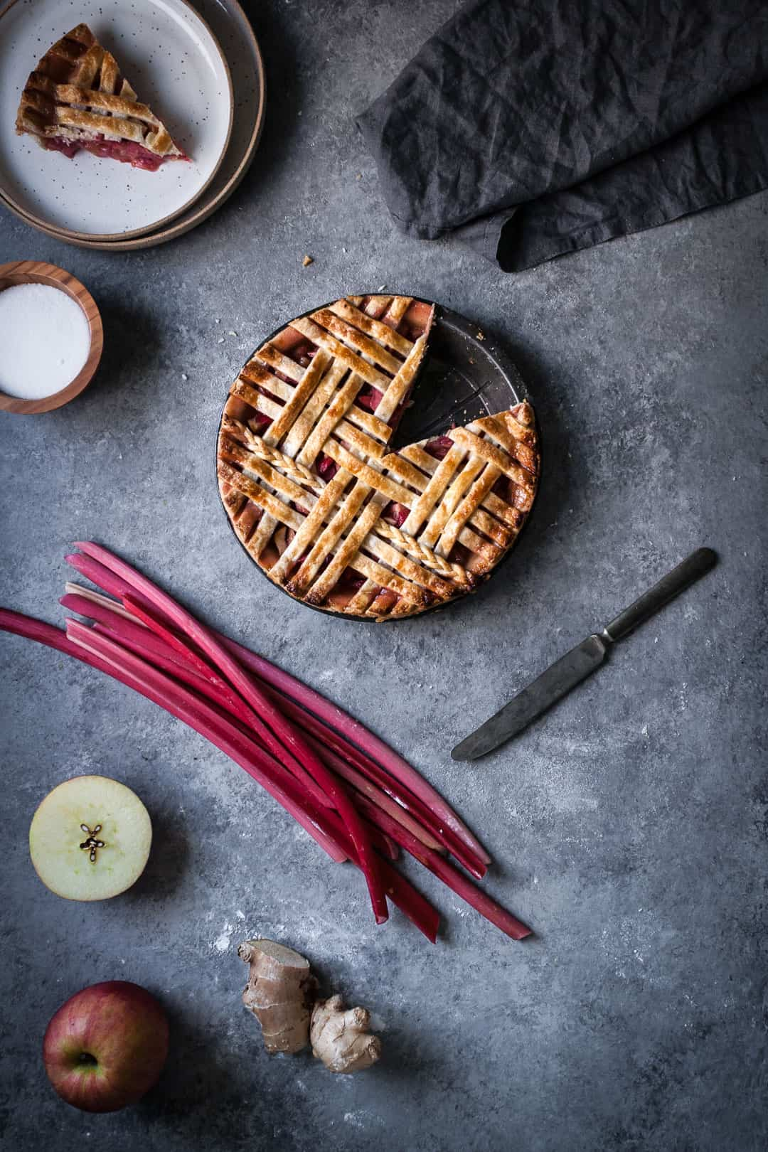 baked rhubarb apple pie with ginger and lemongrass on a grey surface with a piece cut out and the pie ingredients surrounding it