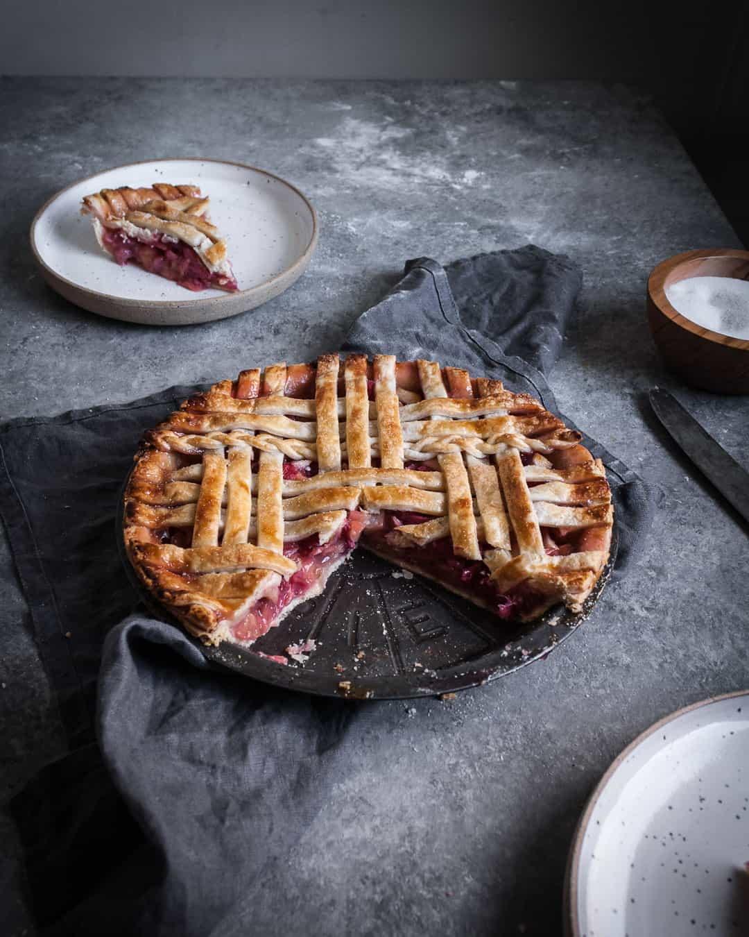 angled shot of rhubarb apple pie with ginger and lemongrass on a grey surface with a piece cut out on a plate and a grey linen towel underneath the pie tin