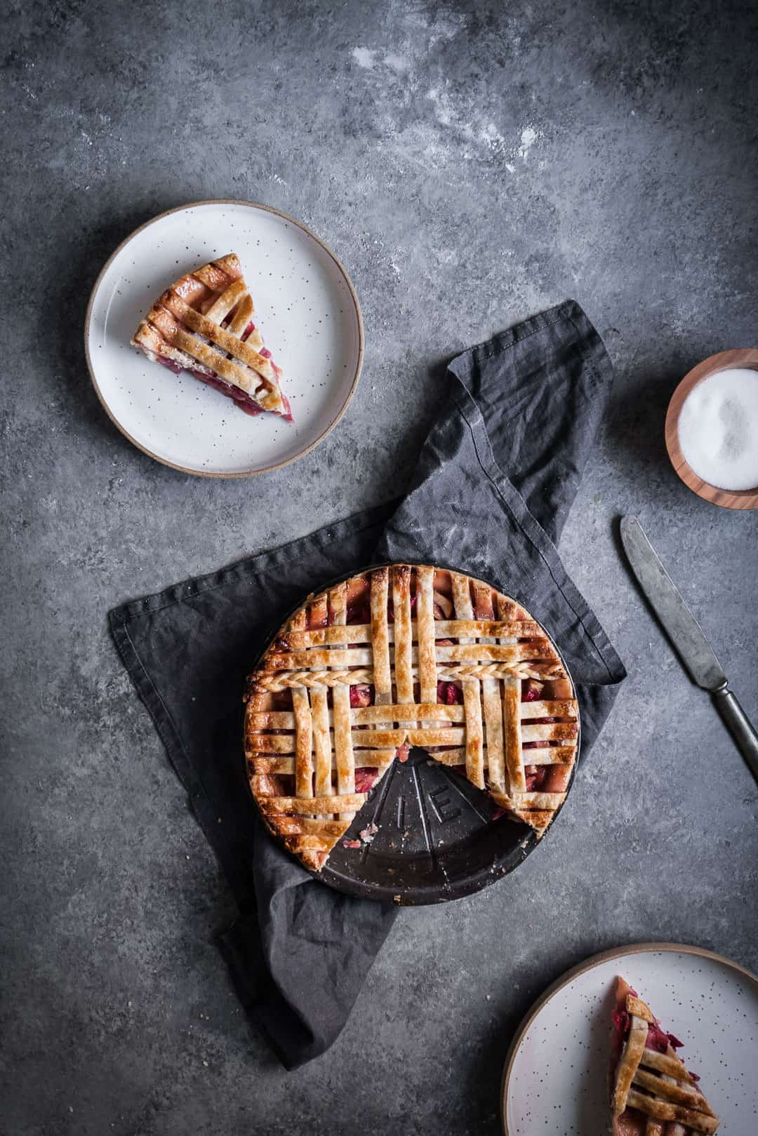 top view of baked rhubarb apple pie with ginger and lemongrass with two pieces cut out and placed on plates nearby, with a grey linen towel under the pie tin