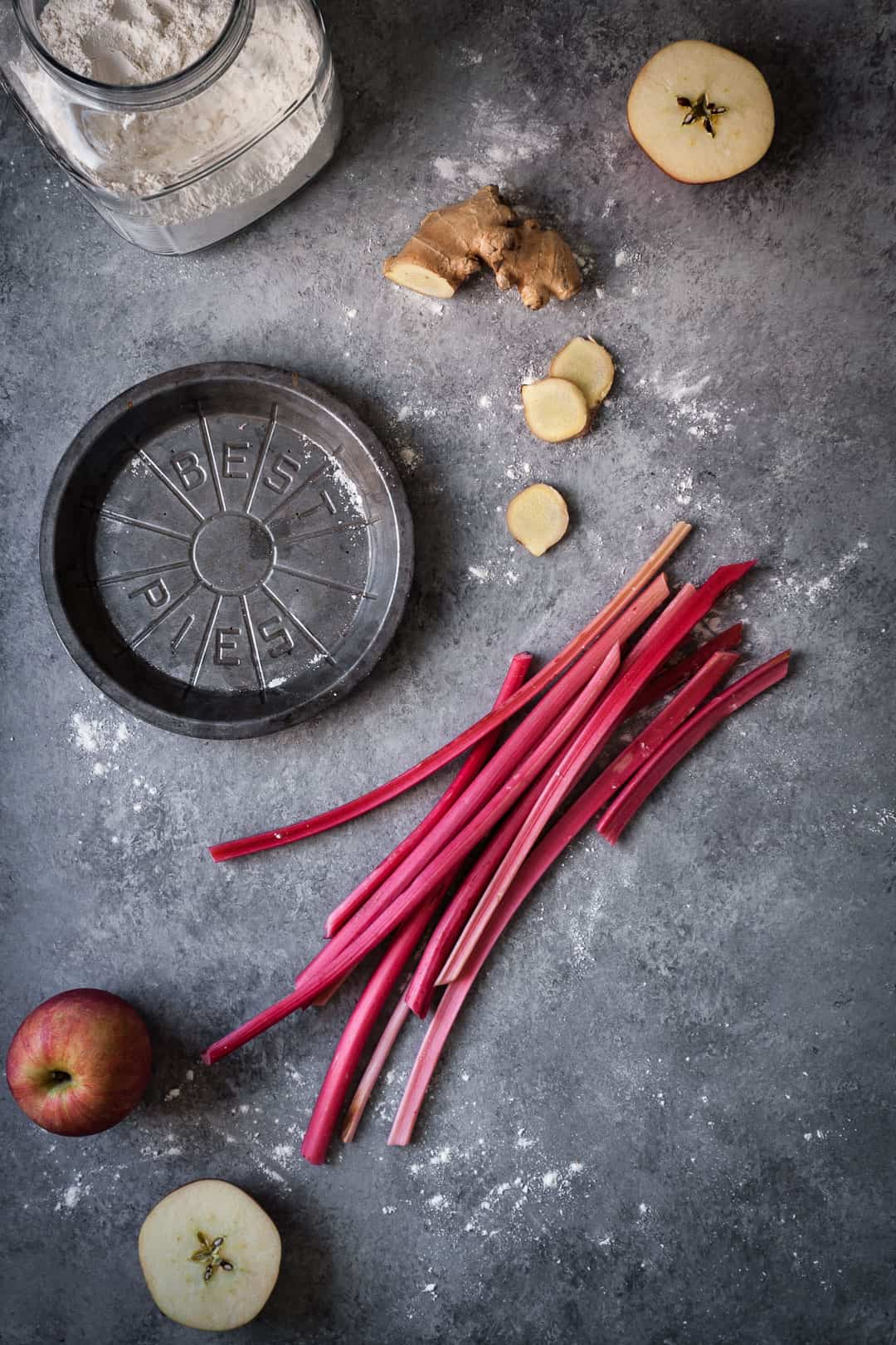 grey surface with metal pie tin and a glass jar of flour along with apples, rhubarb and ginger for rhubarb apple pie with ginger and lemongrass