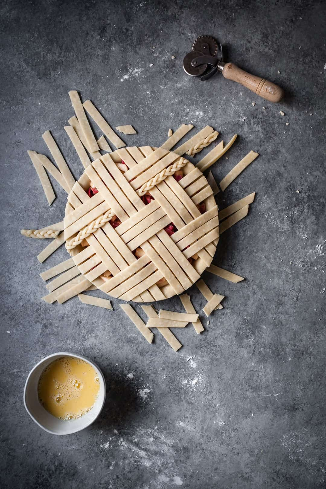 rhubarb apple pie with ginger and lemongrass on a grey surface with lattice top and extra dough trimmings lying near the pie tin