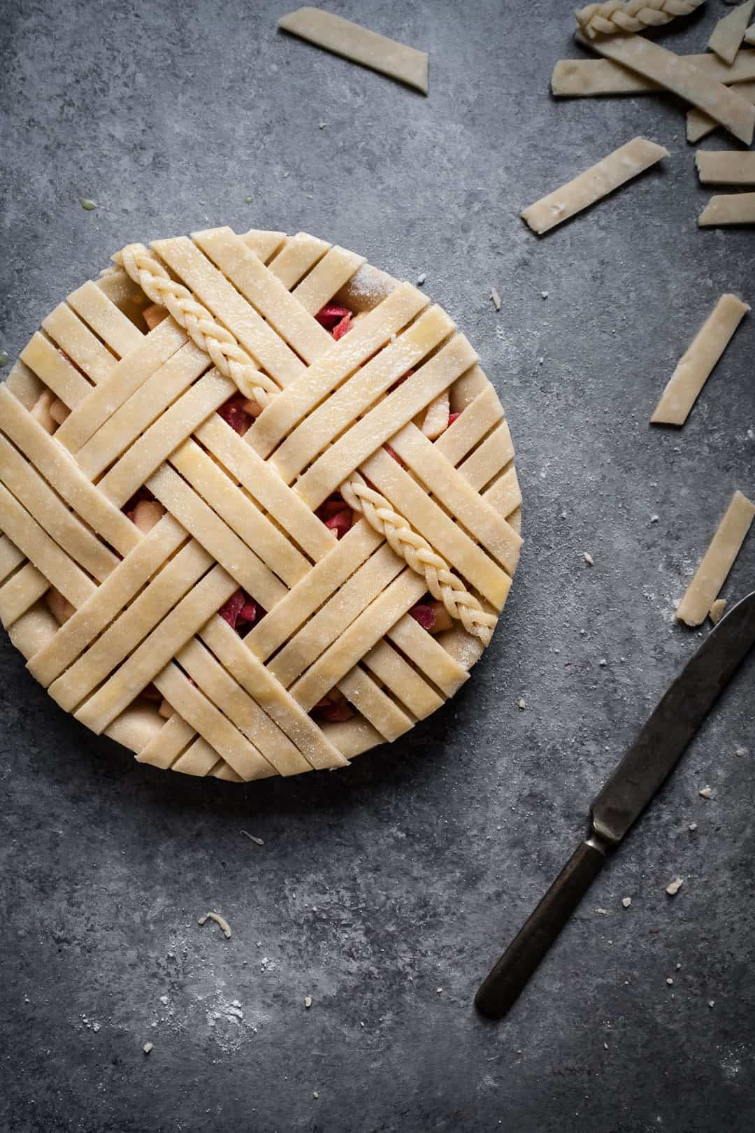 close up on a grey surface of rhubarb apple pie with ginger and lemongrass with lattice top including a small braid of dough
