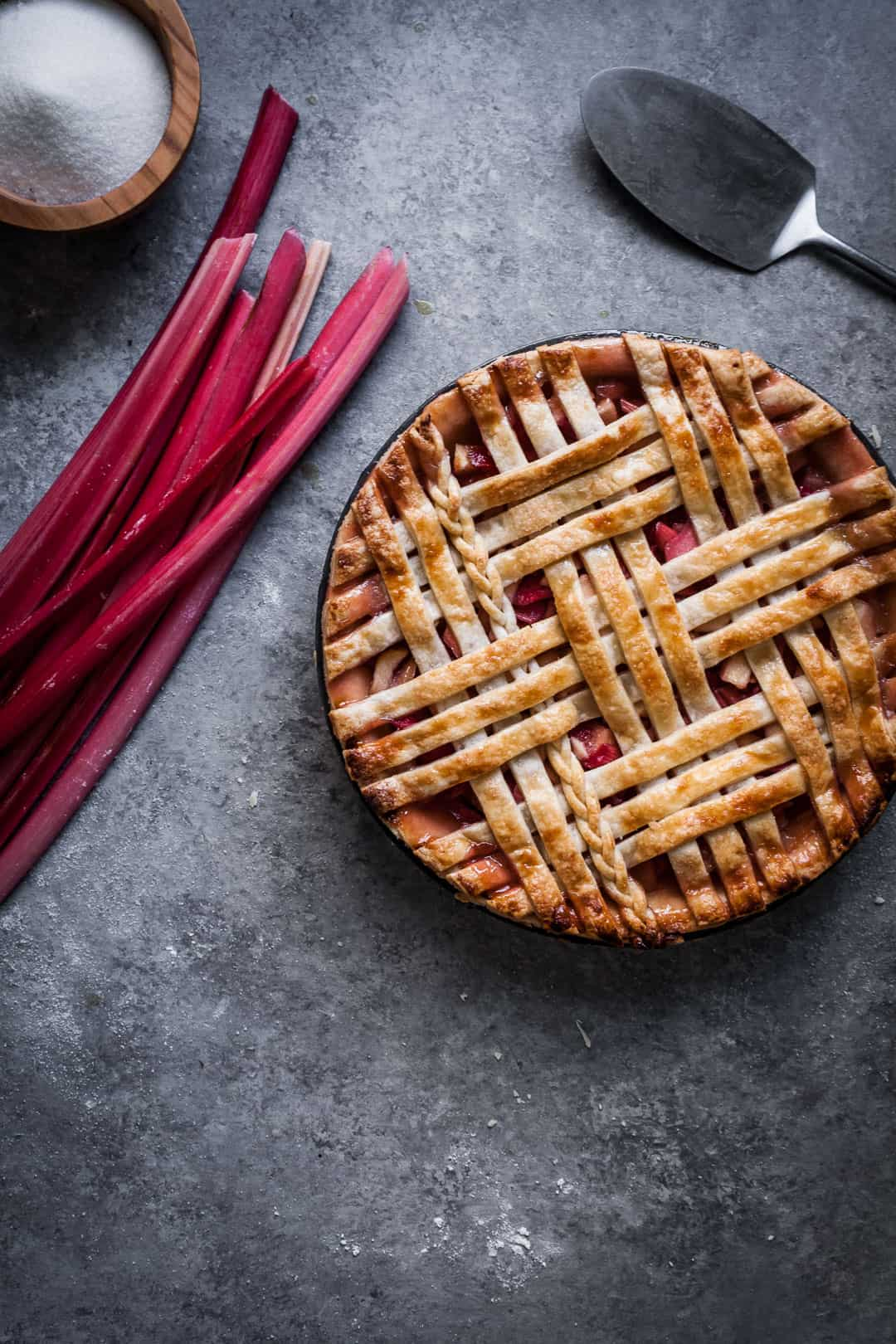 close up on grey background of baked rhubarb apple pie with ginger and lemongrass rhubarb stalks and pie server nearby
