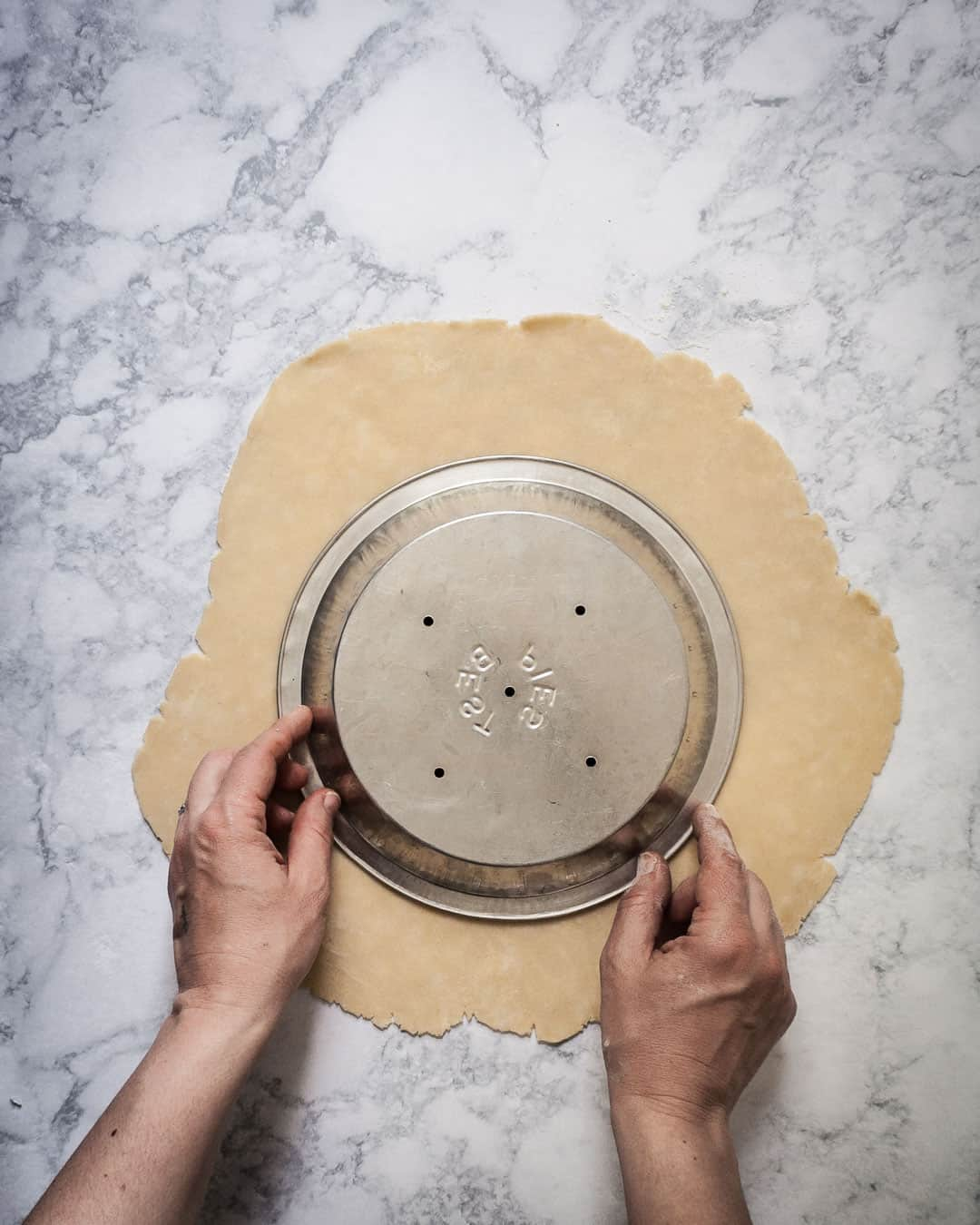 Marble surface with pie dough rolled out and hands holding a metal pie dish to check sizing
