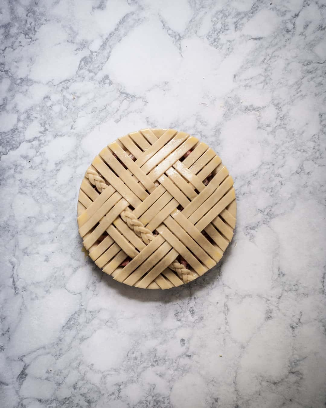 Marble surface and completed lattice pie crust with egg wash brushed on top