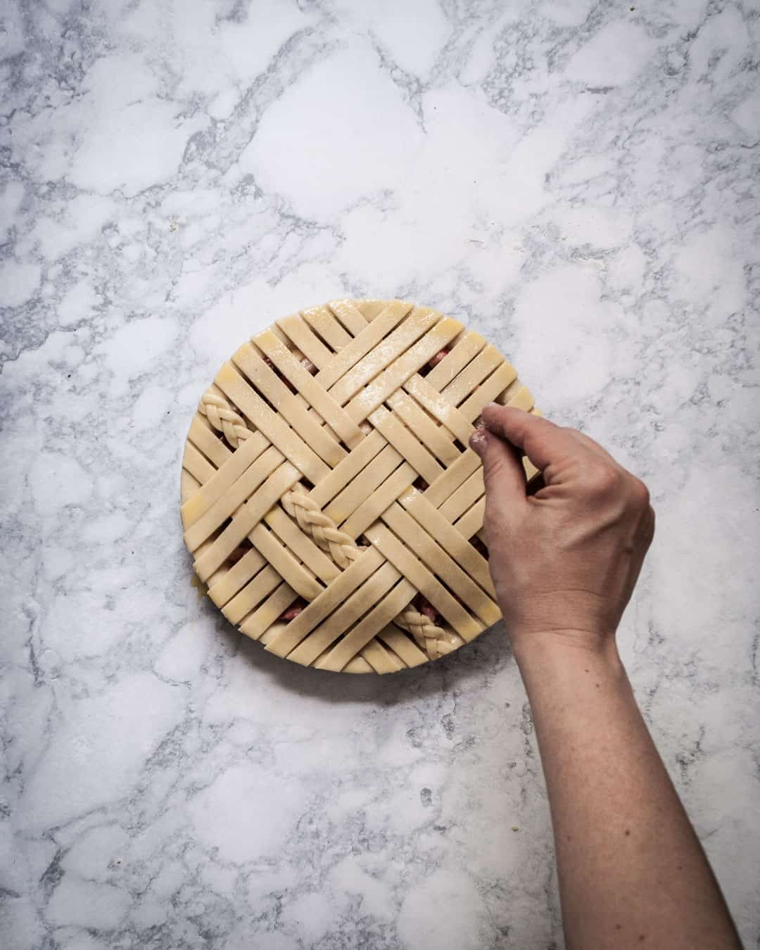 Marble surface with completed lattice pie crust and hand sprinkling sugar on top
