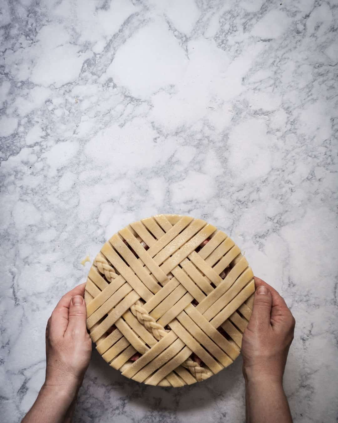 Marble surface and hands removing pie with lattice pie crust for baking