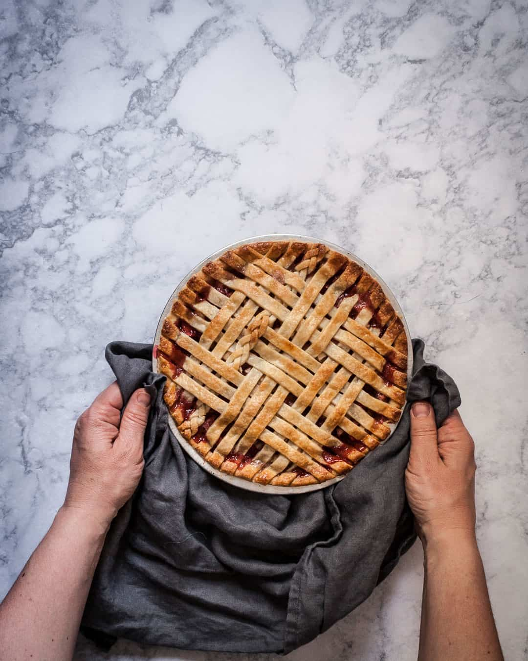 Marble surface with hands holding a baked lattice pie in a grey linen towel