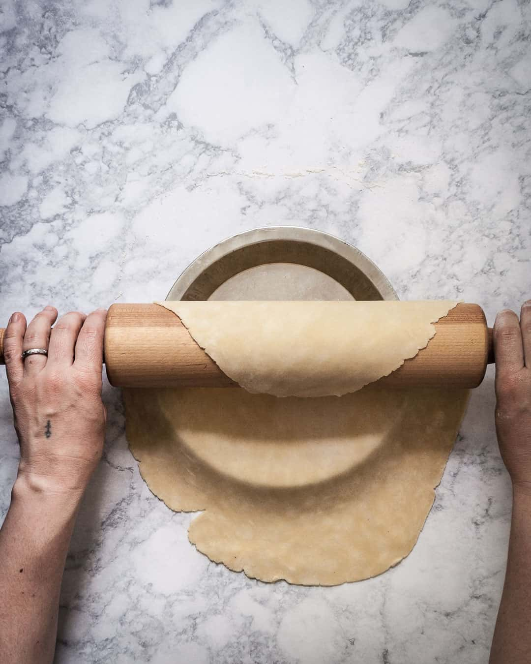 Marble surface with hands holding rolling pin while rolling pie dough out onto pie dish