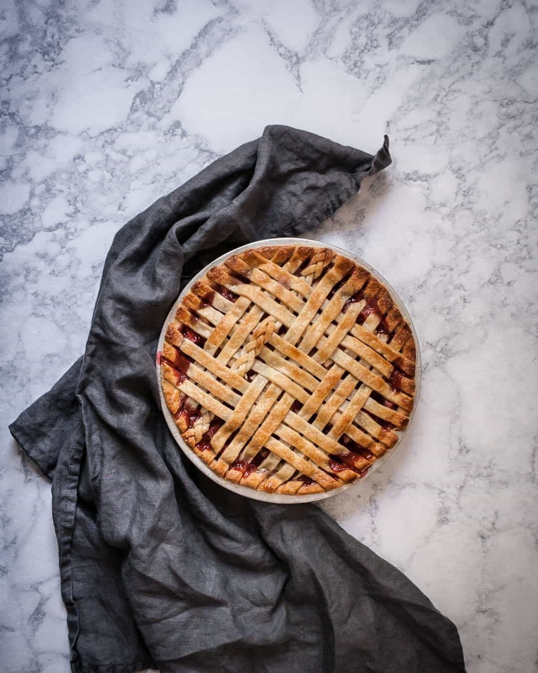 Marble surface with baked lattice pie with a grey linen towel nearby
