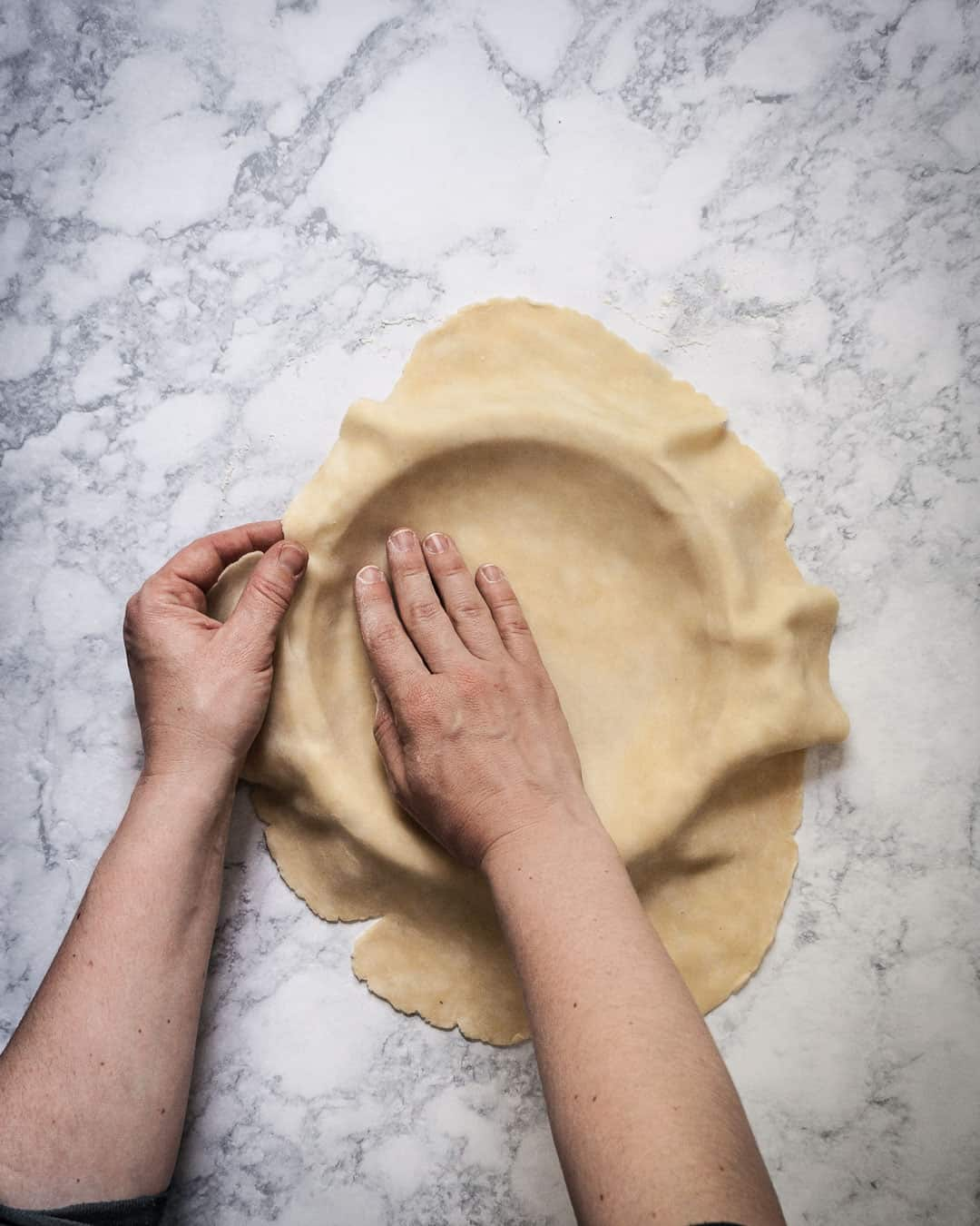 Marble surface with hands pressing pie dough into a pie dish