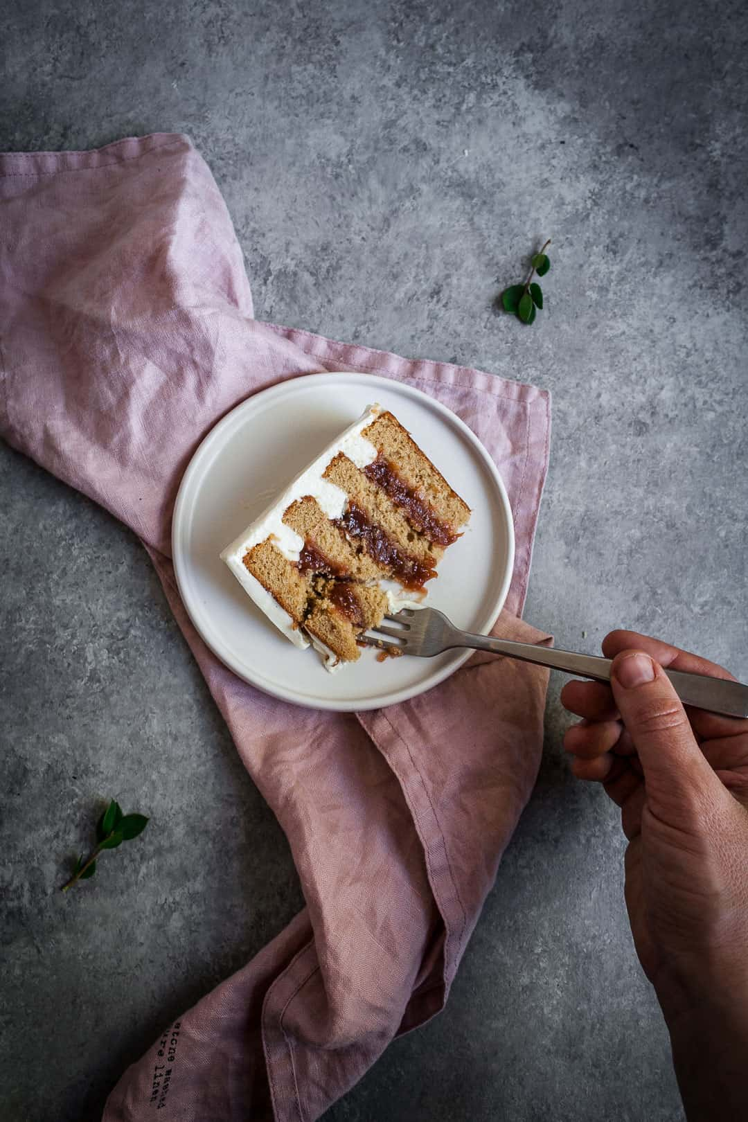Hand holding a fork and cutting into a slice of brown sugar cake with rhubarb compote and creme fraiche buttercream on a pink linen napkin and a grey background