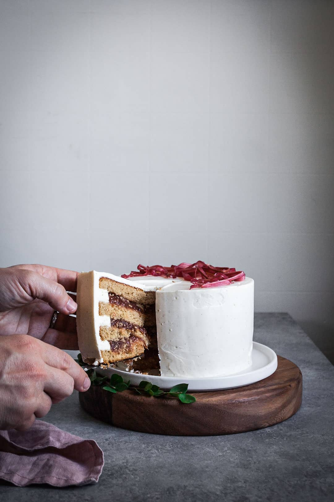 Side view of brown sugar cake with rhubarb compote and creme fraiche buttercream being cut with a knife with two hands in view