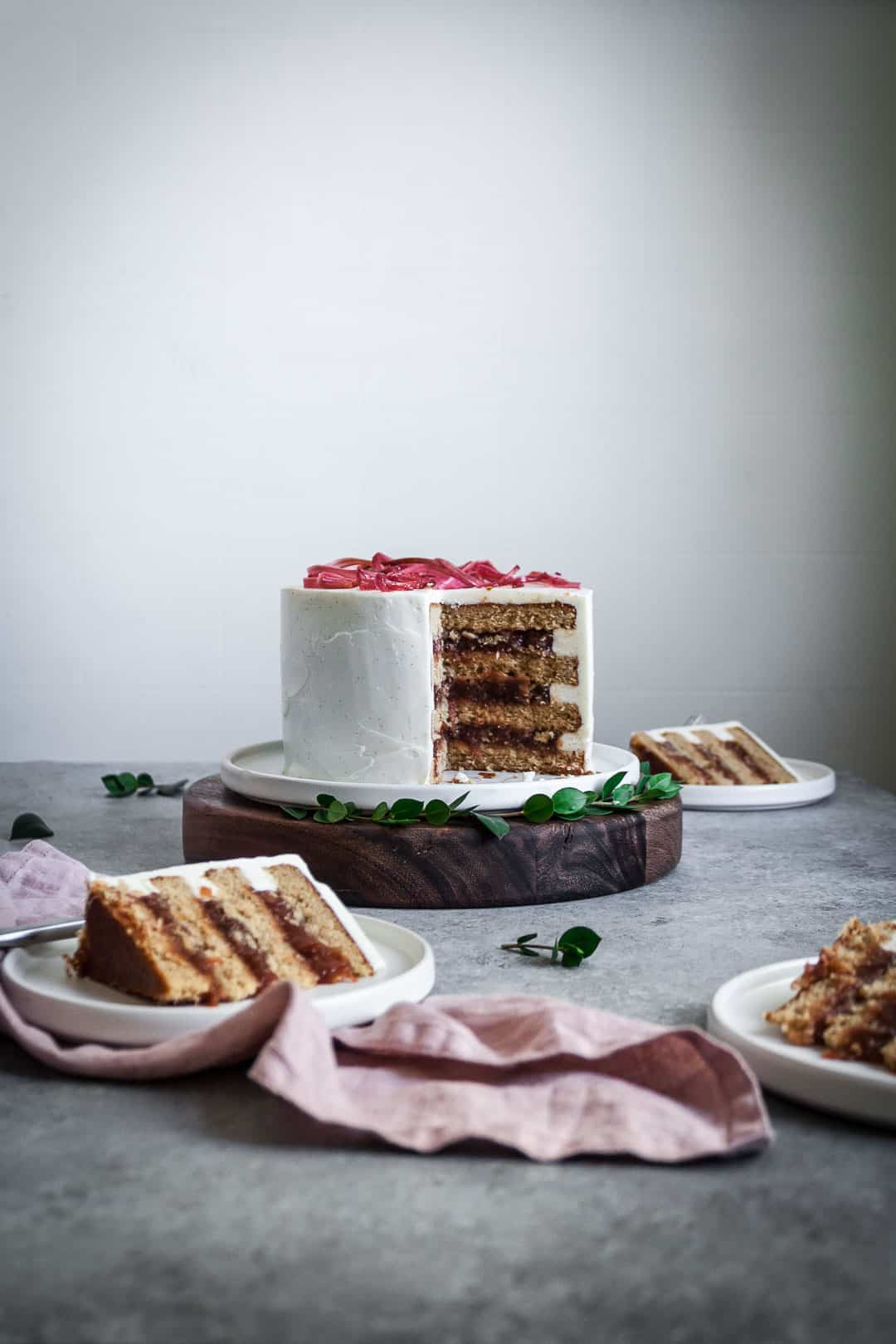 Three slices of brown sugar cake with rhubarb compote and creme fraiche buttercream on plates around the main cake