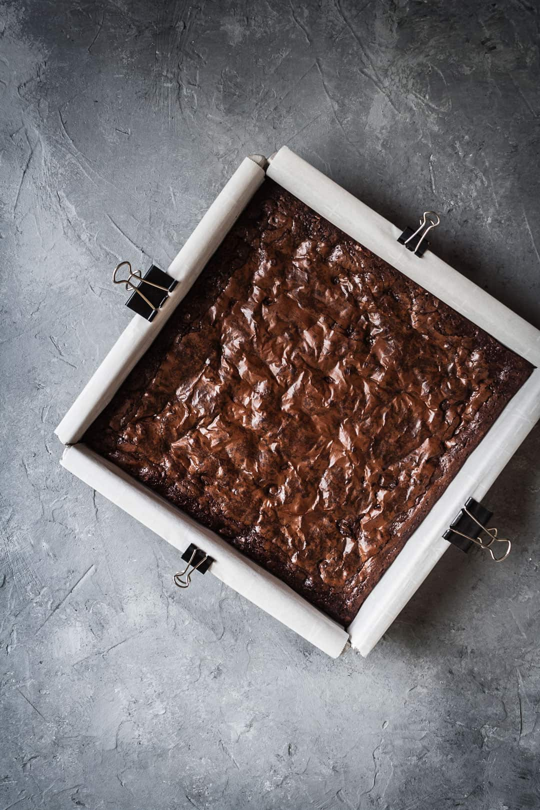 Overhead view of a square pan of brownies with port soaked cherries on a grey background