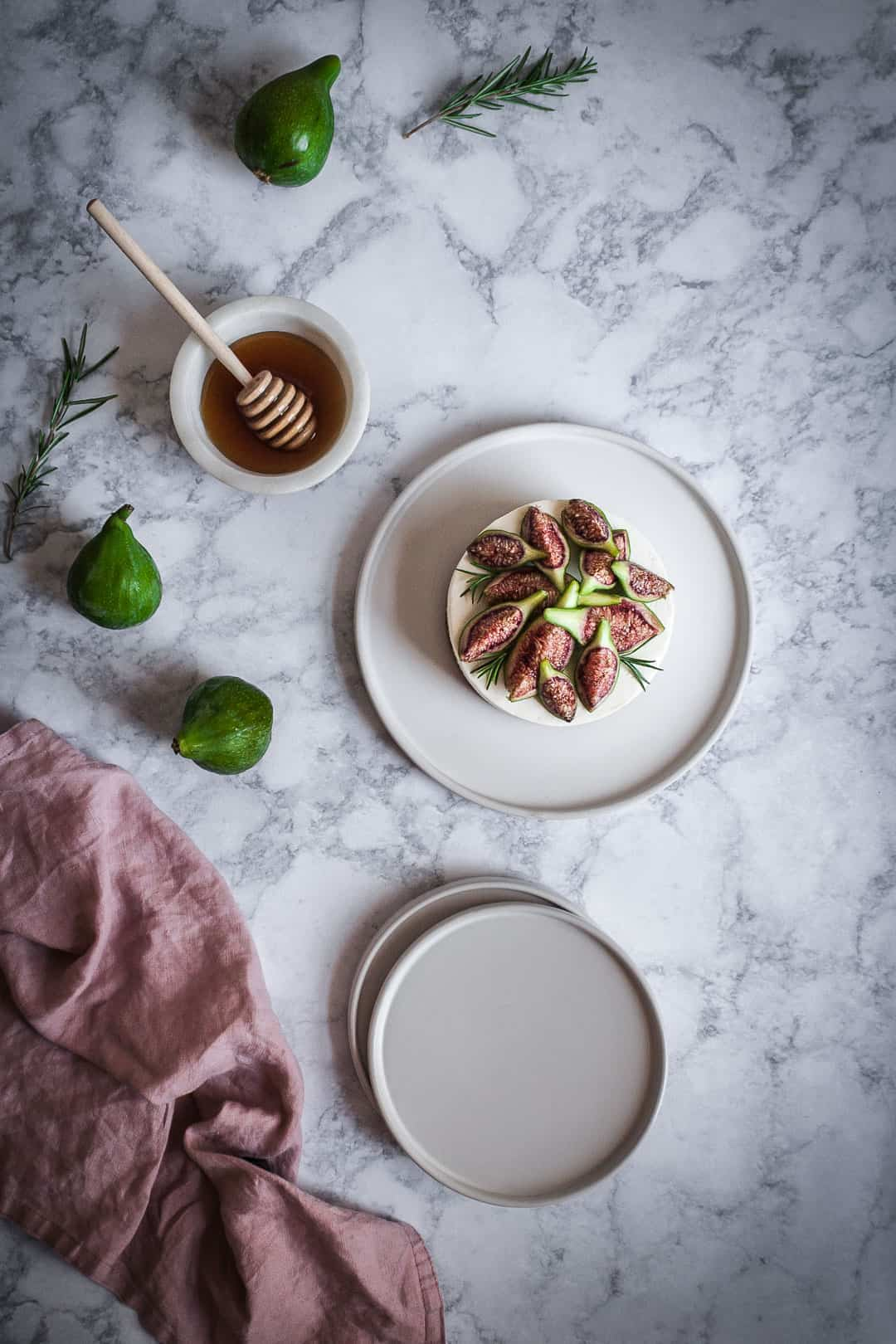 Honey orange cheesecake with figs and rosemary almond crust on a marble backdrop - birds eye view with white plates, green figs and a bowl of honey