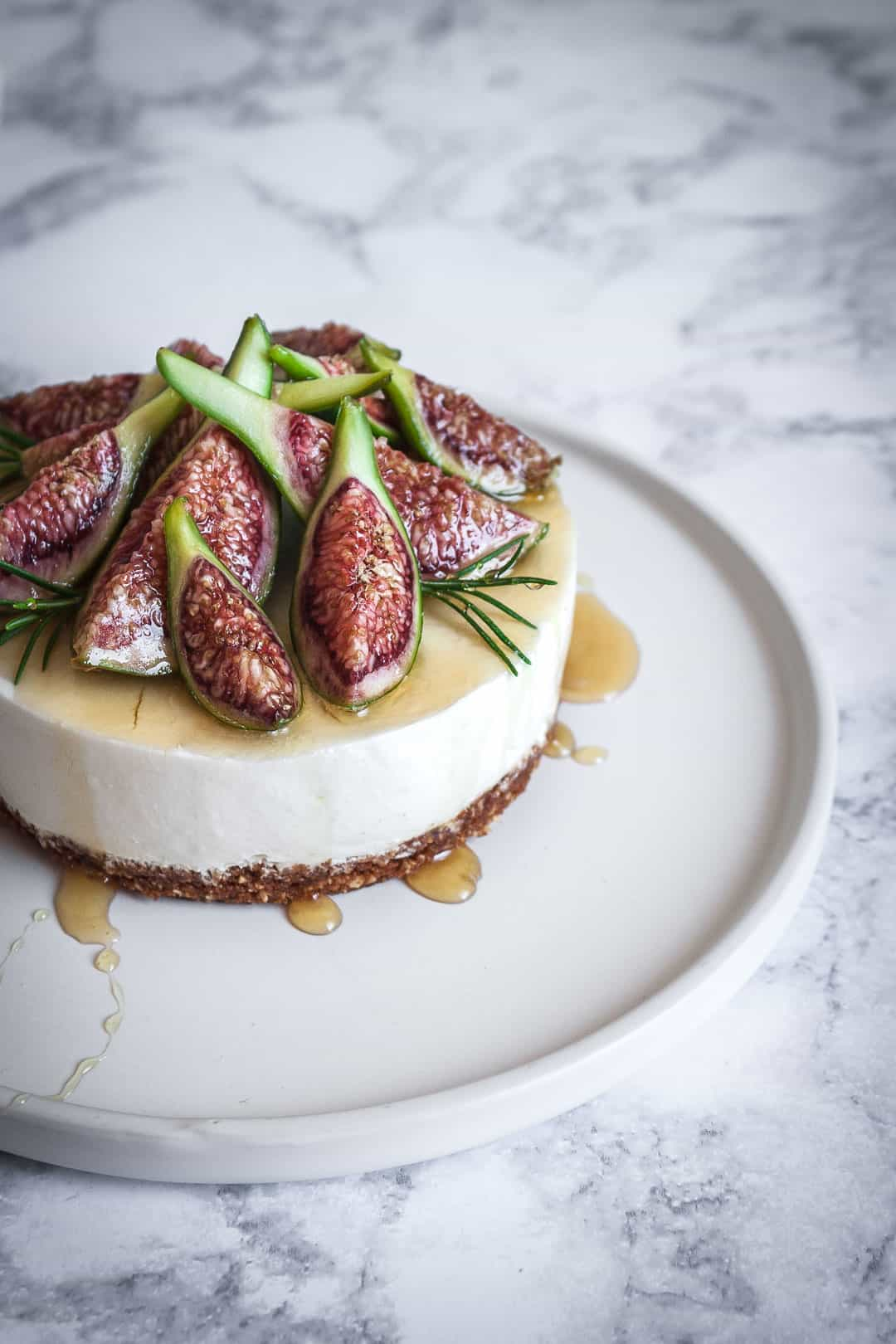 Honey orange cheesecake with figs and rosemary almond crust on a marble backdrop - angled close up view of cheescake with honey drizzled on top