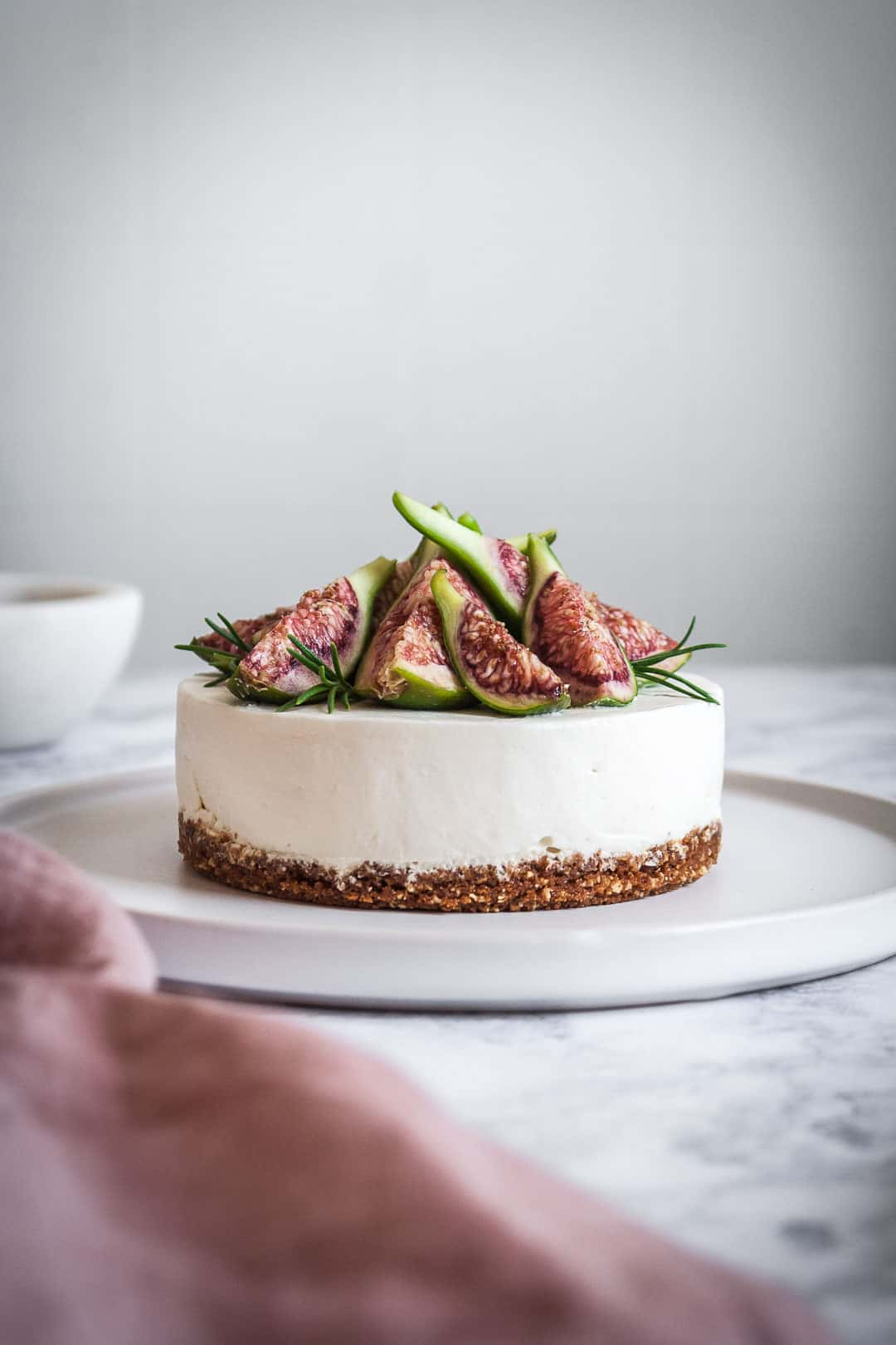 Honey orange cheesecake with figs and rosemary almond crust on a marble backdrop - side view of cheesecake with figs on top