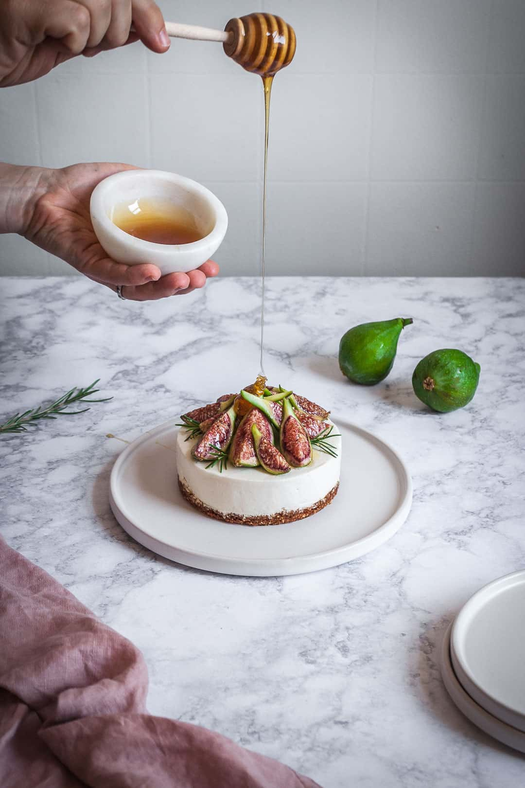 Honey orange cheesecake with figs and rosemary almond crust on a marble backdrop - angled shot of hand holding honey bowl drizzling honey with white plates, green figs