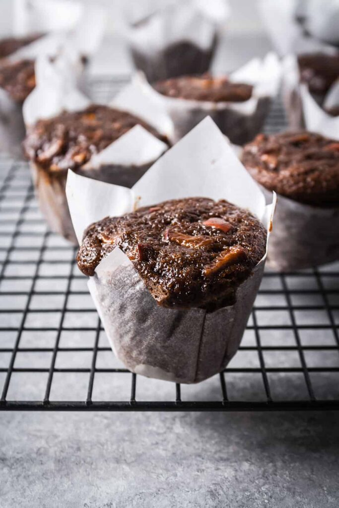 Apple ginger mini cakes in parchment paper cups with more cakes on a rack in the background