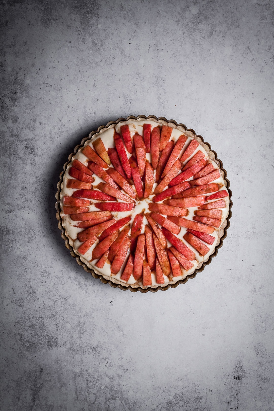 Pink Apple Tart with Cream Cheese Filling on a grey background - prior to baking