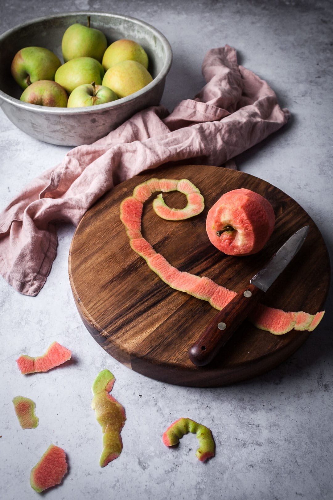 Peeled pink apple on a wooden cutting board and a grey background - prep shot for Pink Apple Tart with Cream Cheese Filling