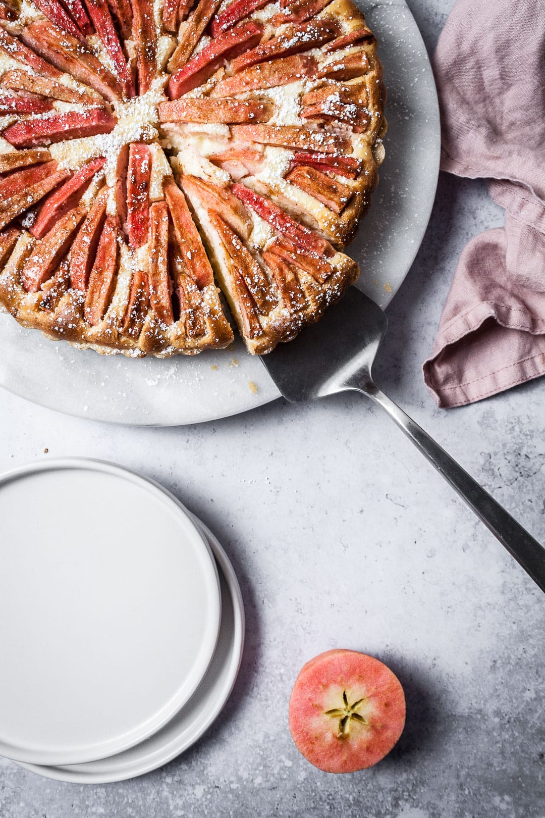 Closeup shot of Pink Apple Tart with Cream Cheese Filling with a slice being lifted off of the marble serving platter; white plates nearby