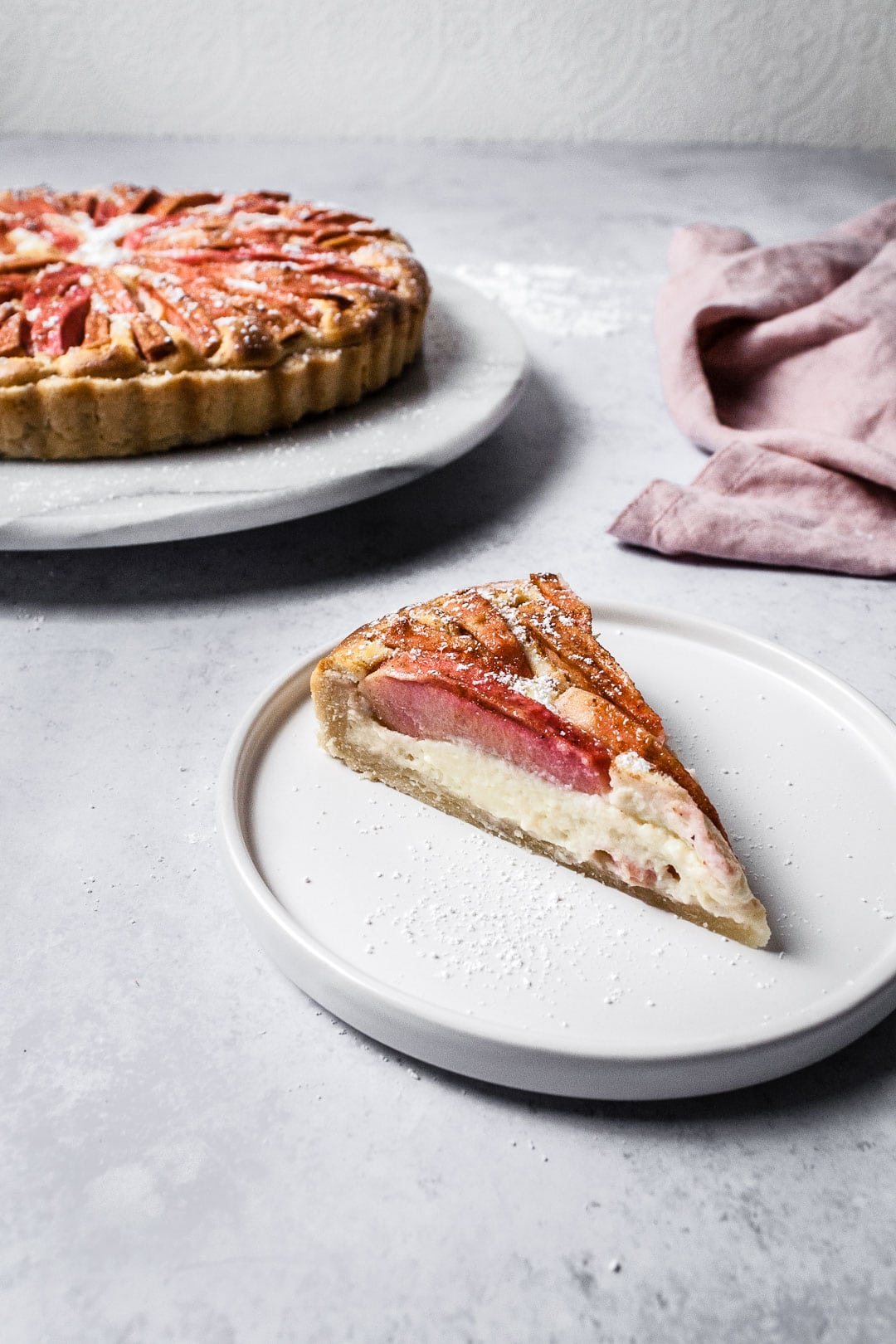 Slice of Pink Apple Tart with Cream Cheese Filling on a white plate and a grey background with whole tart behind it