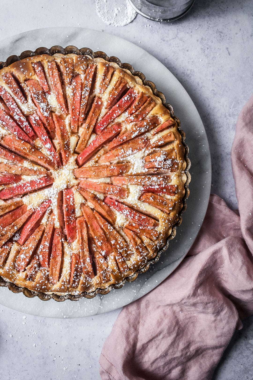 Pink Apple Tart with Cream Cheese Filling on a marble platter with a grey background