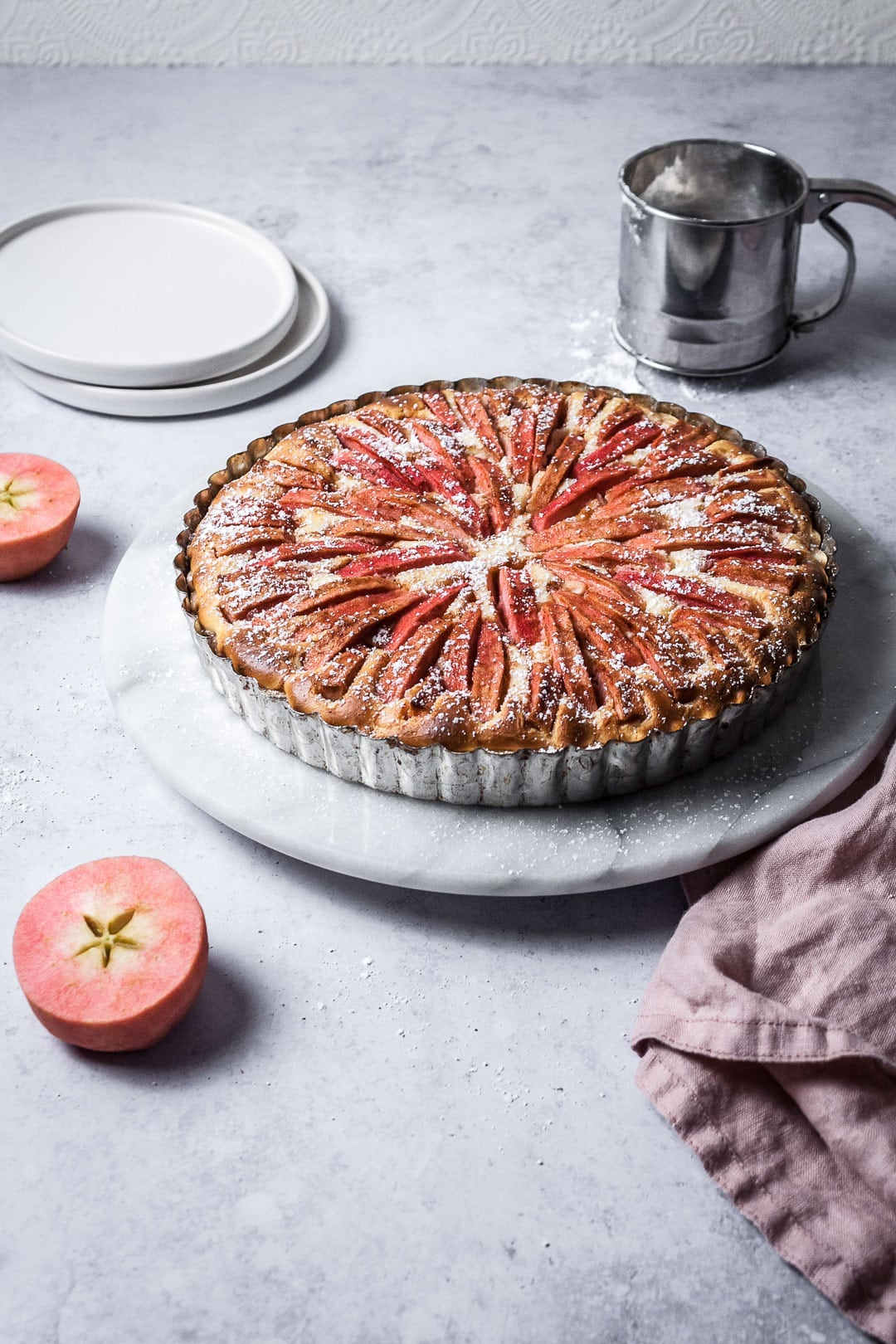 Pink Apple Tart with Cream Cheese Filling on a marble cake stand with a grey background; pink apples cut in half nearby
