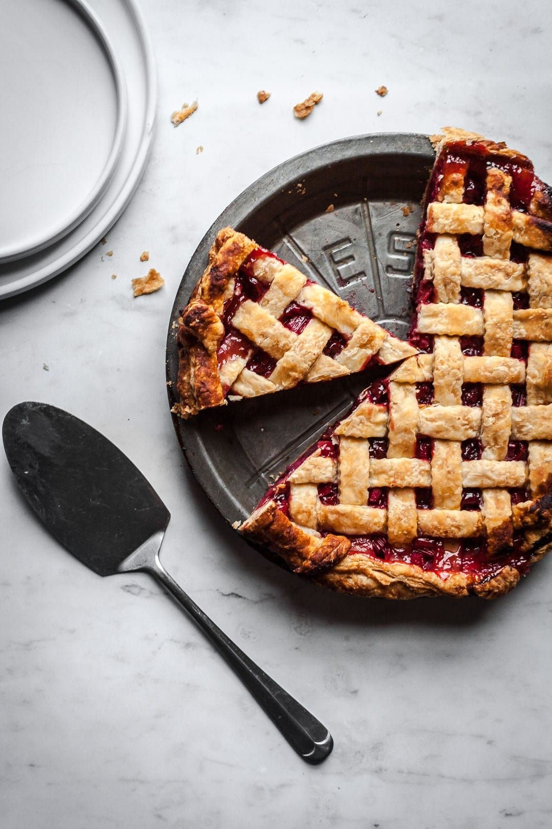 Top view of lattice crust pie with two slices cut out and serving utensil and plates nearby
