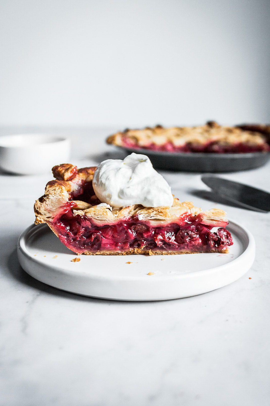 Slice of cherry rhubarb pie from side, with pie tin and serving utensils in background
