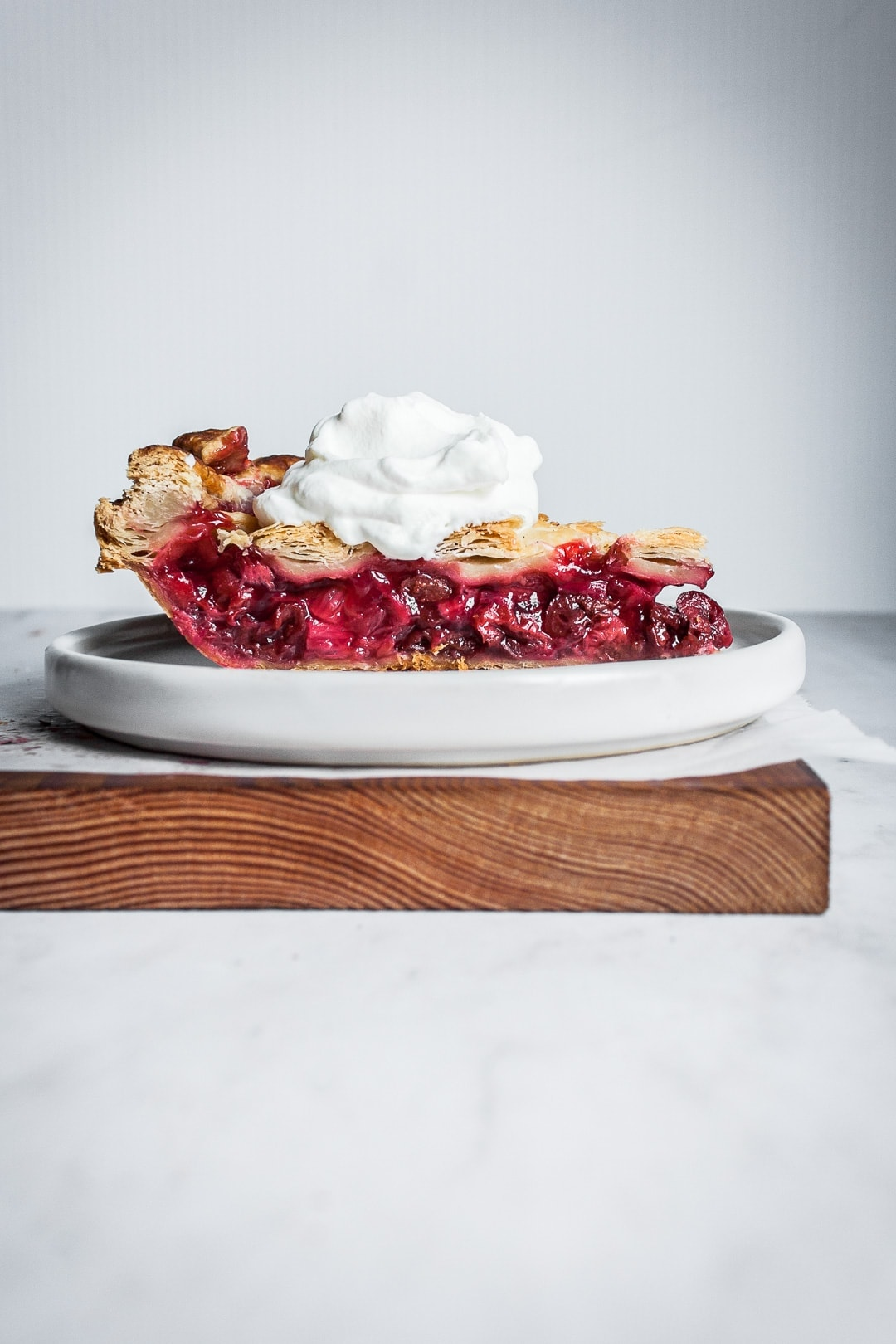 Side view of a slice of cherry rhubarb pie on a white plate with a spoonful of whipped cream on top