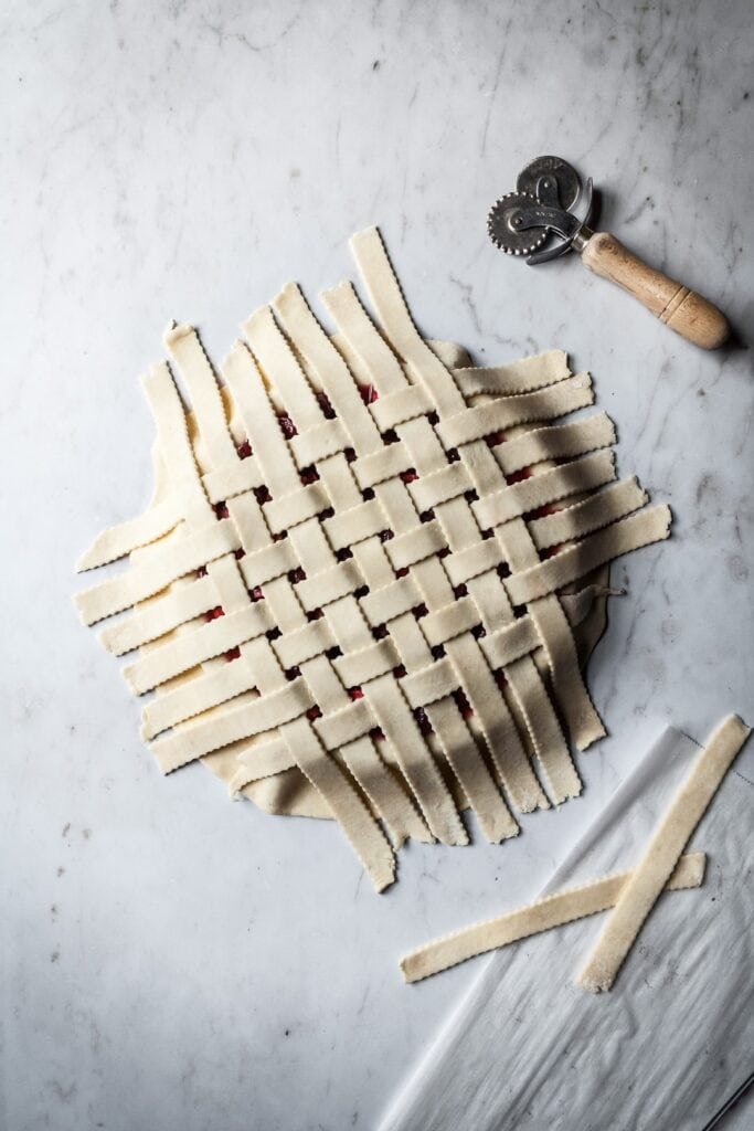 Top view of lattice pie crust with pastry cutter and extra lattice pieces nearby