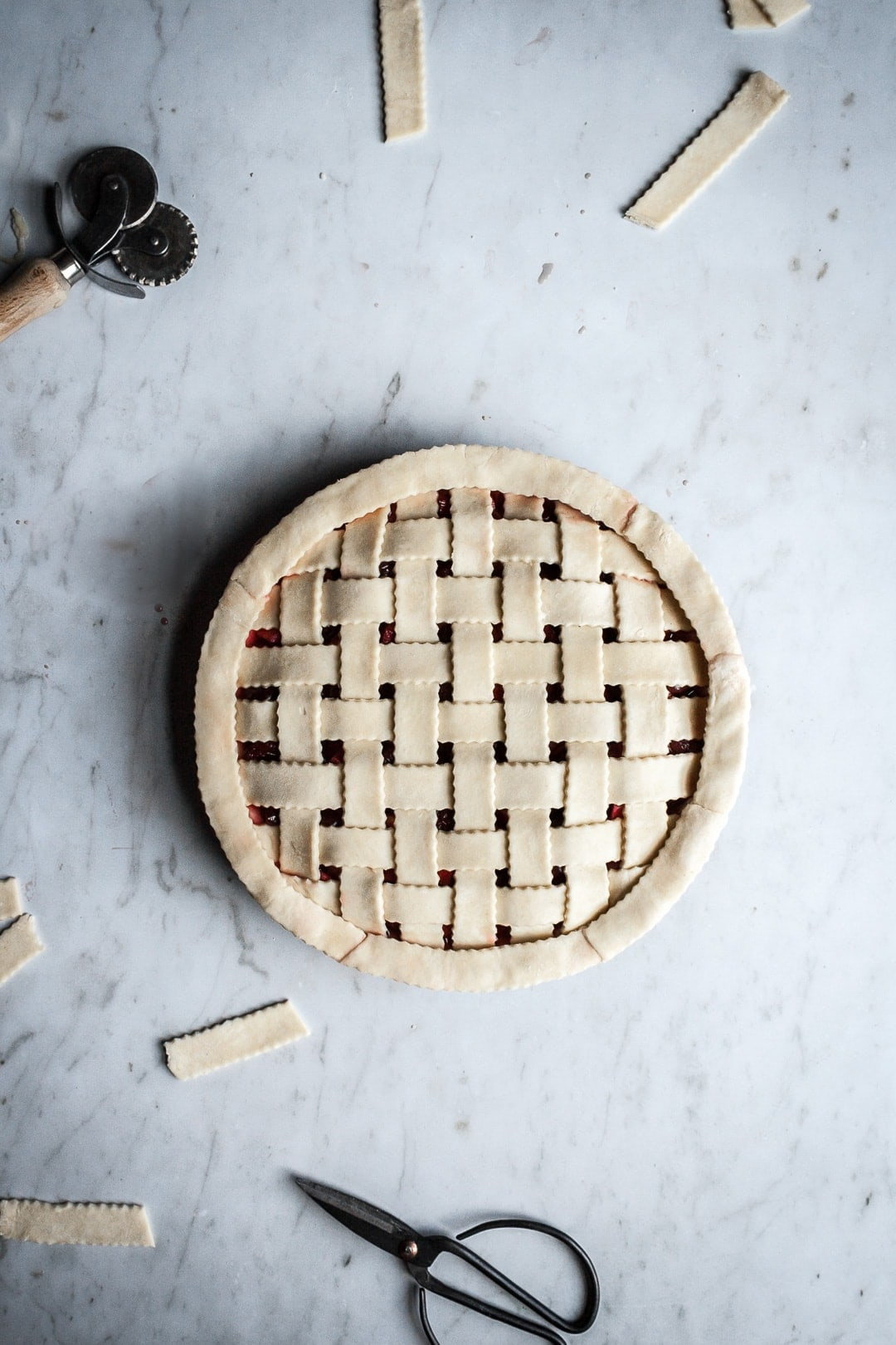 Top view of pie with lattice crust under construction on a marble background