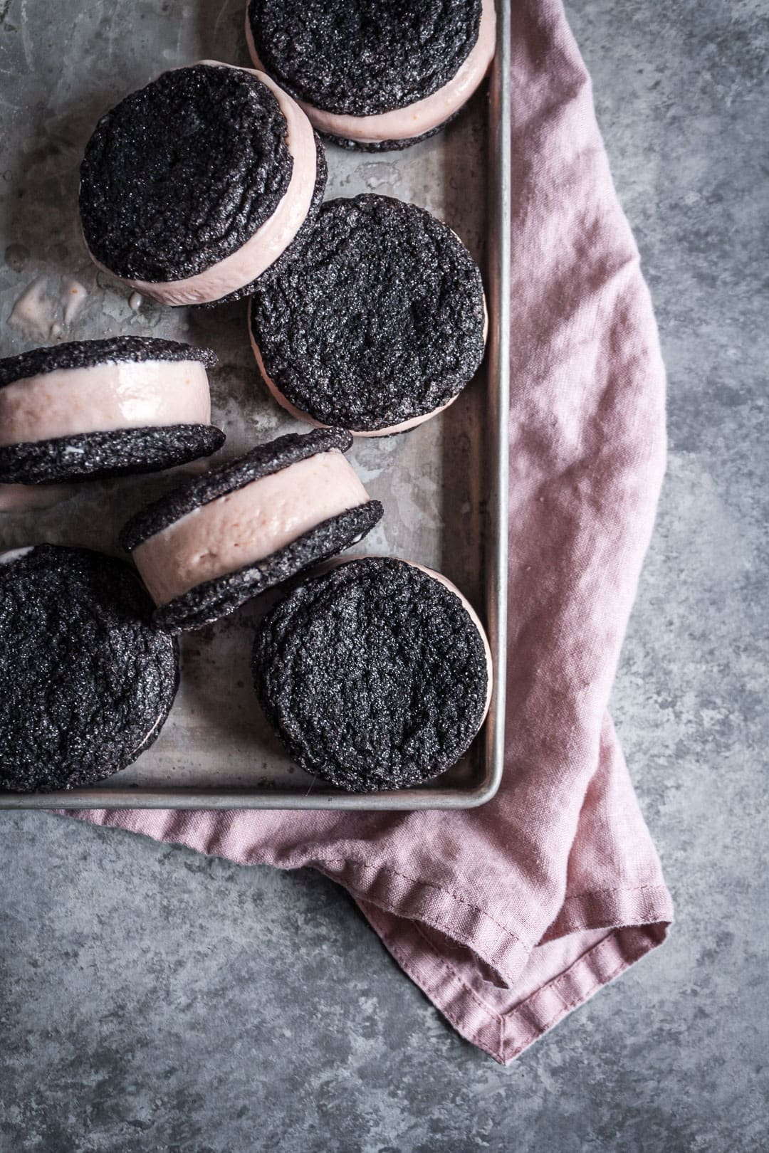 Top view of metal tray filled with chocolate blood orange ice cream sandwiches with pink linen napkin