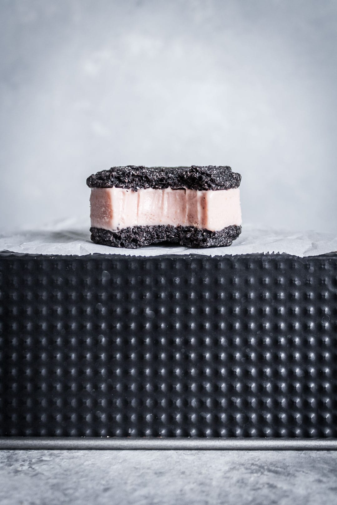 Side view of chocolate blood orange ice cream sandwich with bite taken out, resting on parchment paper and a black metal tin